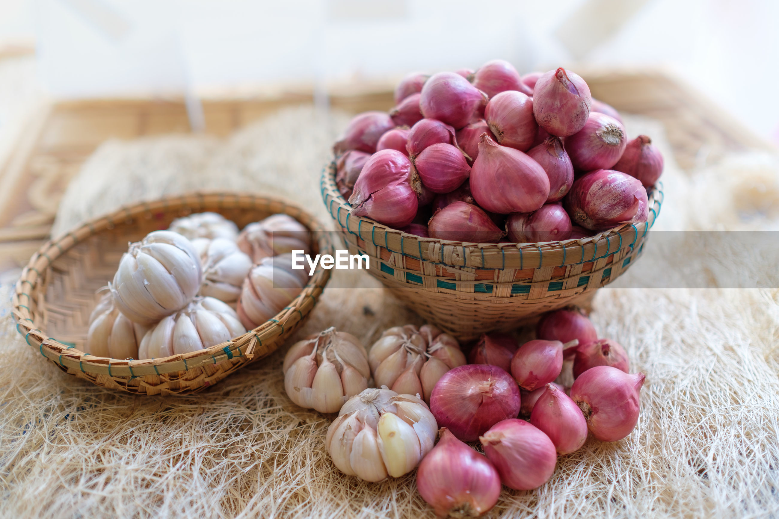 High angle view of onion and garlic in basket on table
