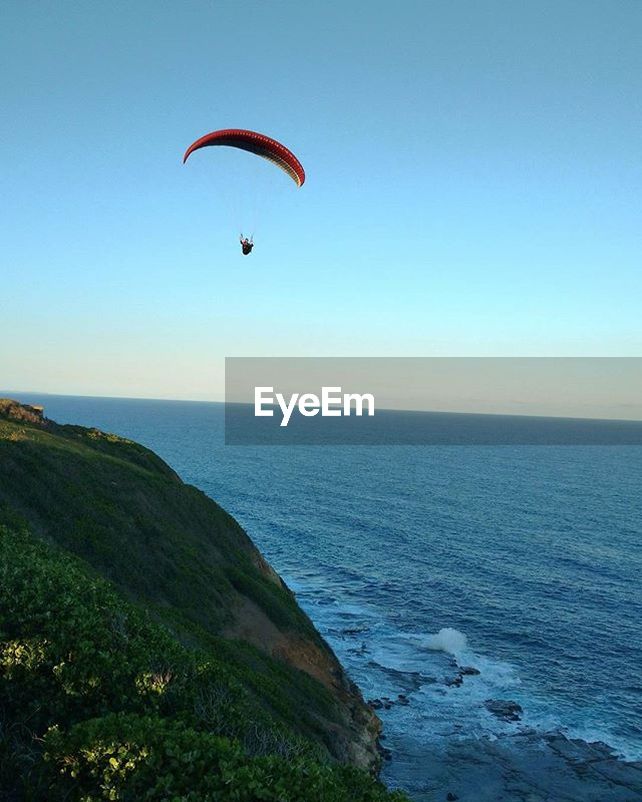 sea, horizon over water, clear sky, beach, tranquil scene, water, scenics, tranquility, mid-air, flying, copy space, beauty in nature, parachute, blue, nature, paragliding, sky, shore, vacations, idyllic