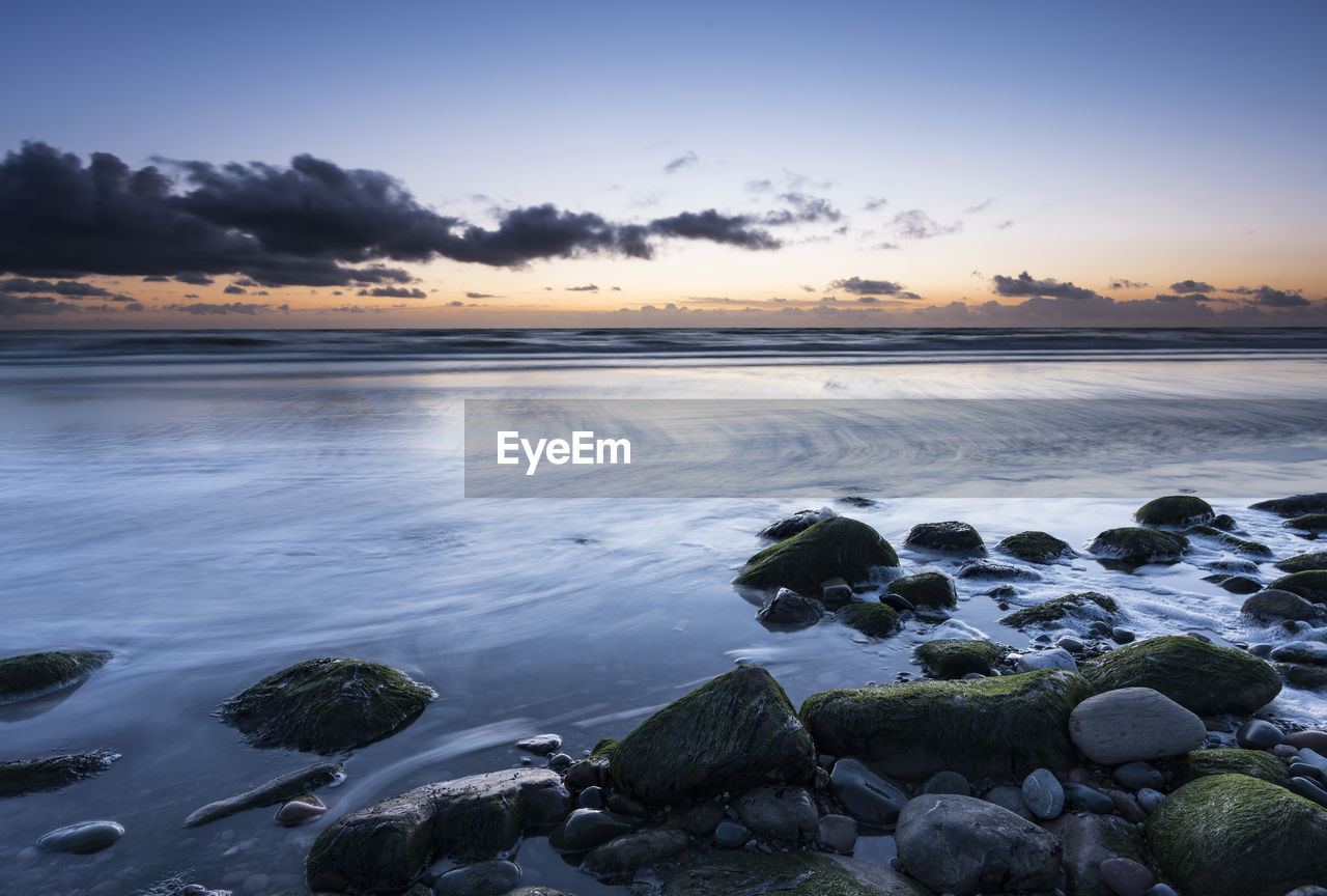 water, sky, beauty in nature, scenics - nature, solid, rock, tranquil scene, sunset, tranquility, rock - object, sea, beach, cloud - sky, no people, nature, idyllic, land, non-urban scene