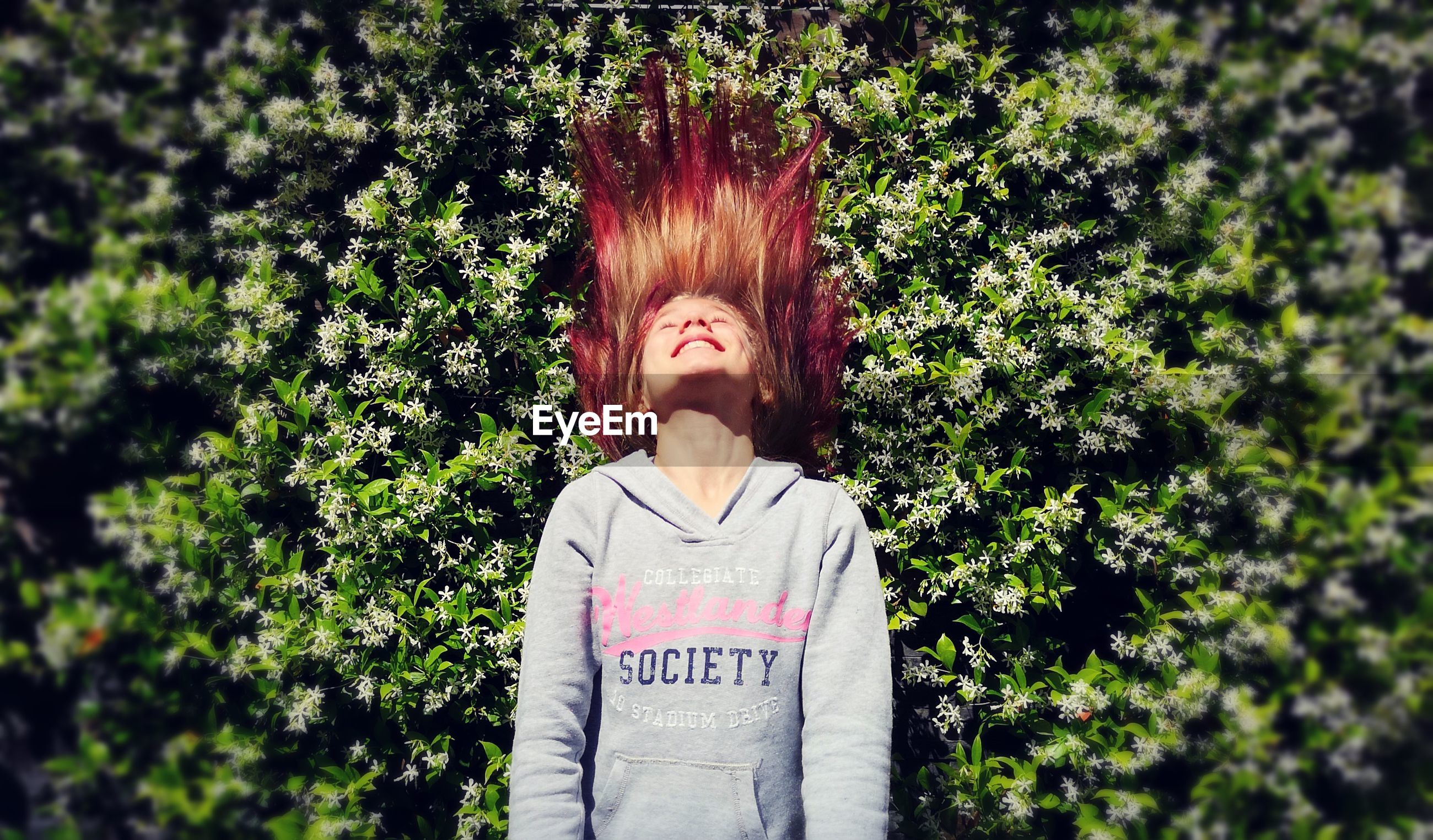 Smiling teenage girl tossing hair while standing against plants