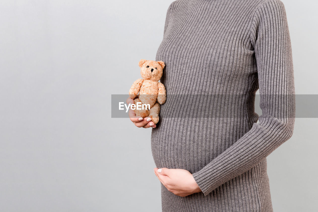 MIDSECTION OF A PERSON HOLDING TOY