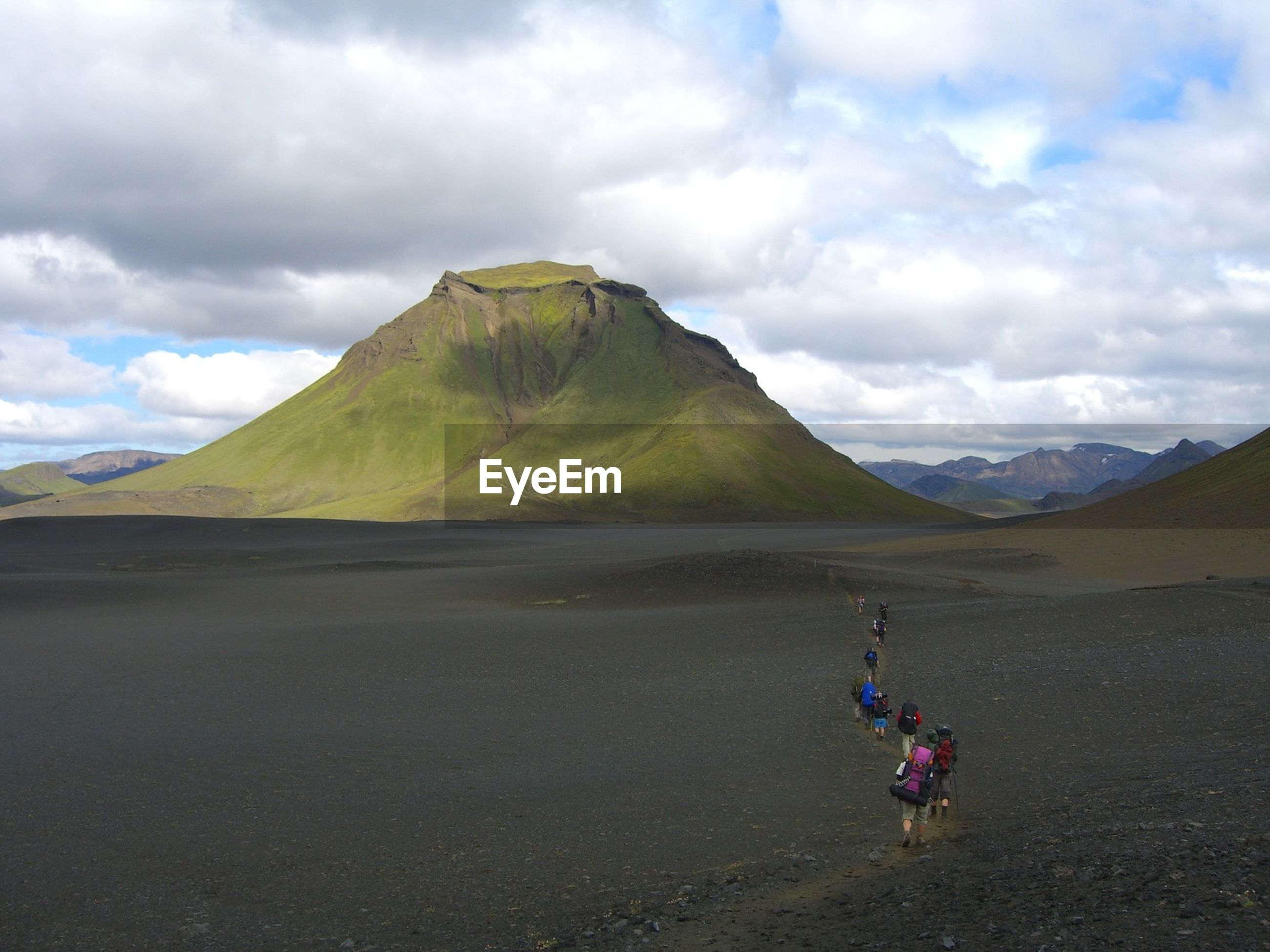 People walking on landscape against mountains