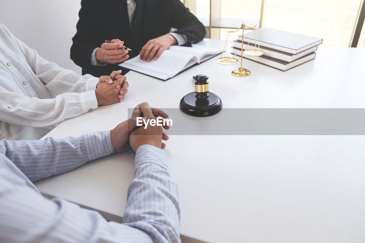 Cropped Image Of Lawyer With Men Sitting At Table
