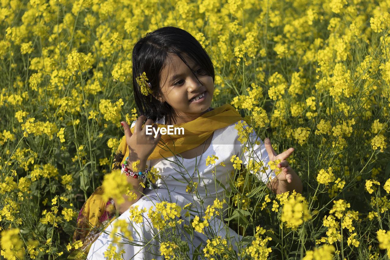 PORTRAIT OF HAPPY GIRL STANDING ON YELLOW FLOWERING PLANTS