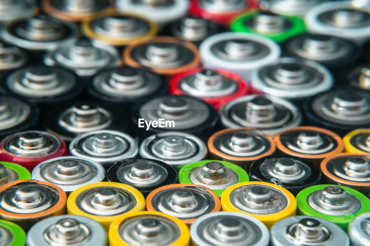 full frame, large group of objects, backgrounds, no people, indoors, side by side, in a row, arrangement, abundance, close-up, order, still life, high angle view, repetition, multi colored, selective focus, shape, container, pattern, bottle