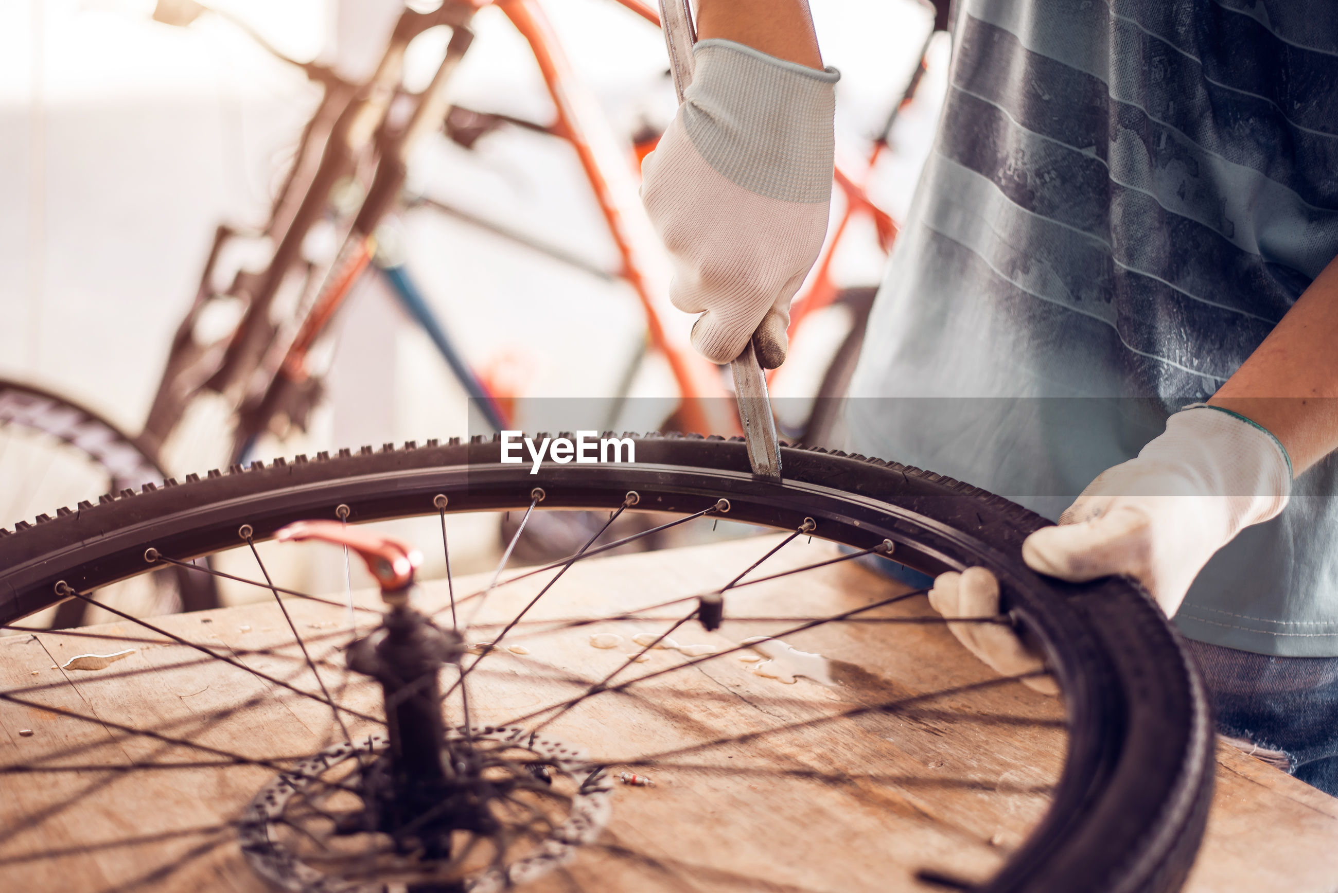 Midsection of man repairing bicycle tire