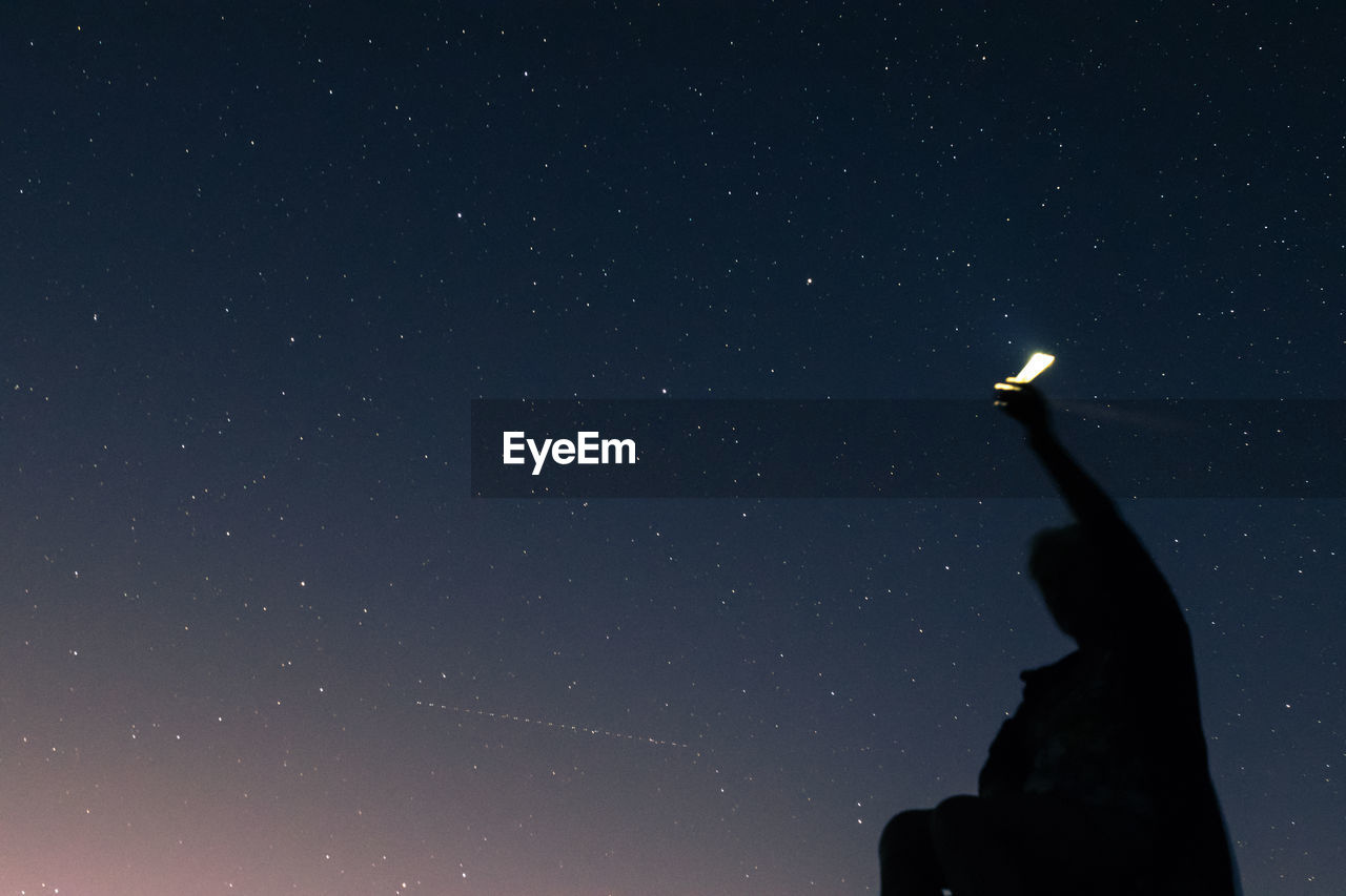 Low Angle View Of Silhouette Man Holding Illuminated Flashlight Against Star Field