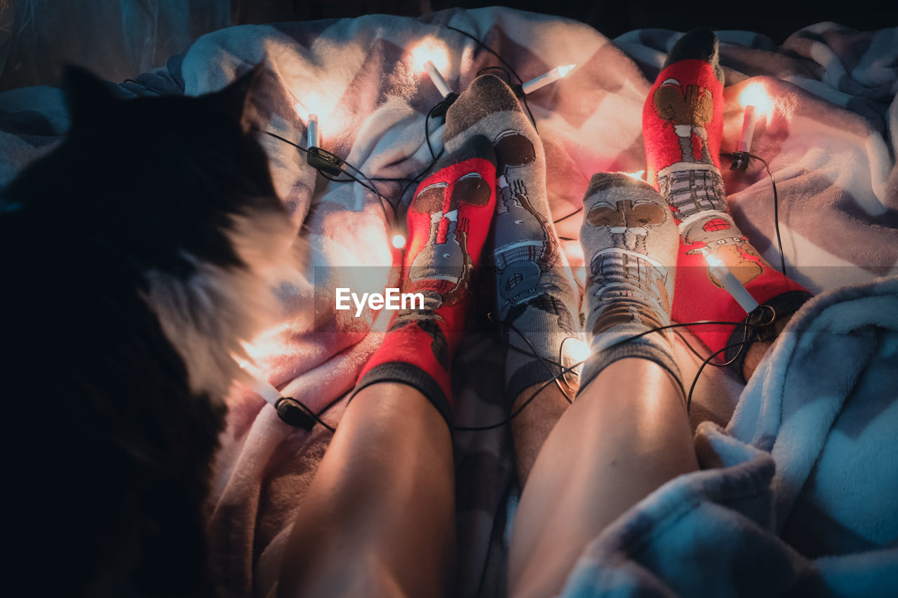 Low section of people wearing socks with illuminated string lights sitting on bed