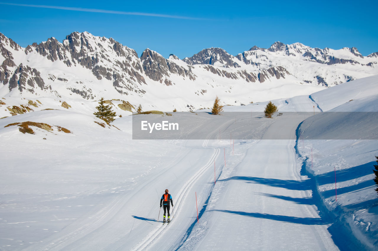 Rear view of man skiing on snow covered land