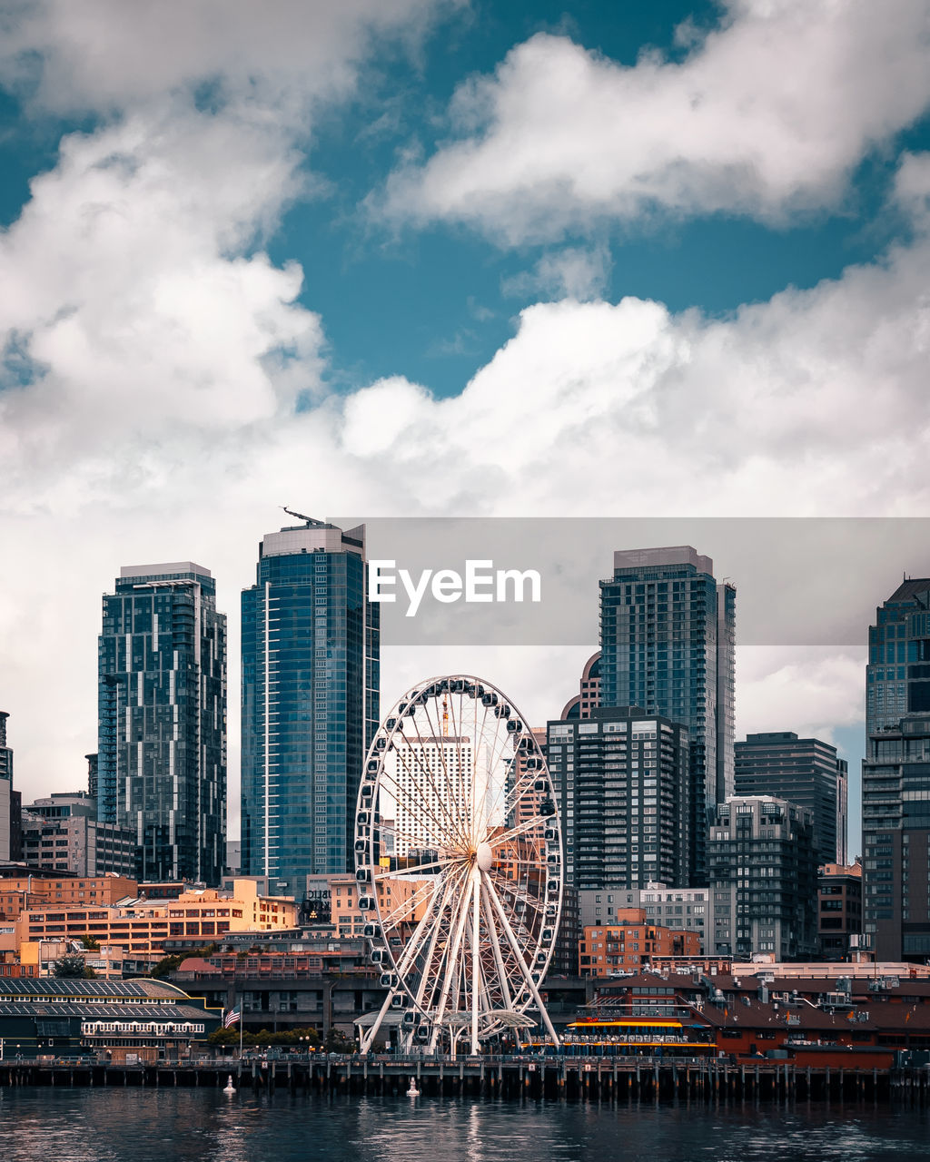 building exterior, built structure, architecture, city, cloud - sky, sky, ferris wheel, building, amusement park ride, office building exterior, amusement park, water, skyscraper, travel destinations, modern, tall - high, nature, cityscape, no people, outdoors, financial district