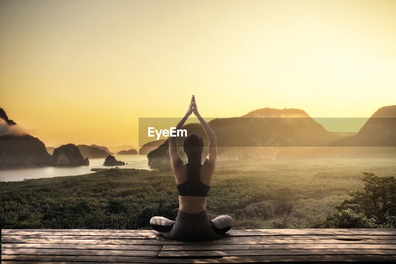 Woman doing yoga on boardwalk against sky during sunset