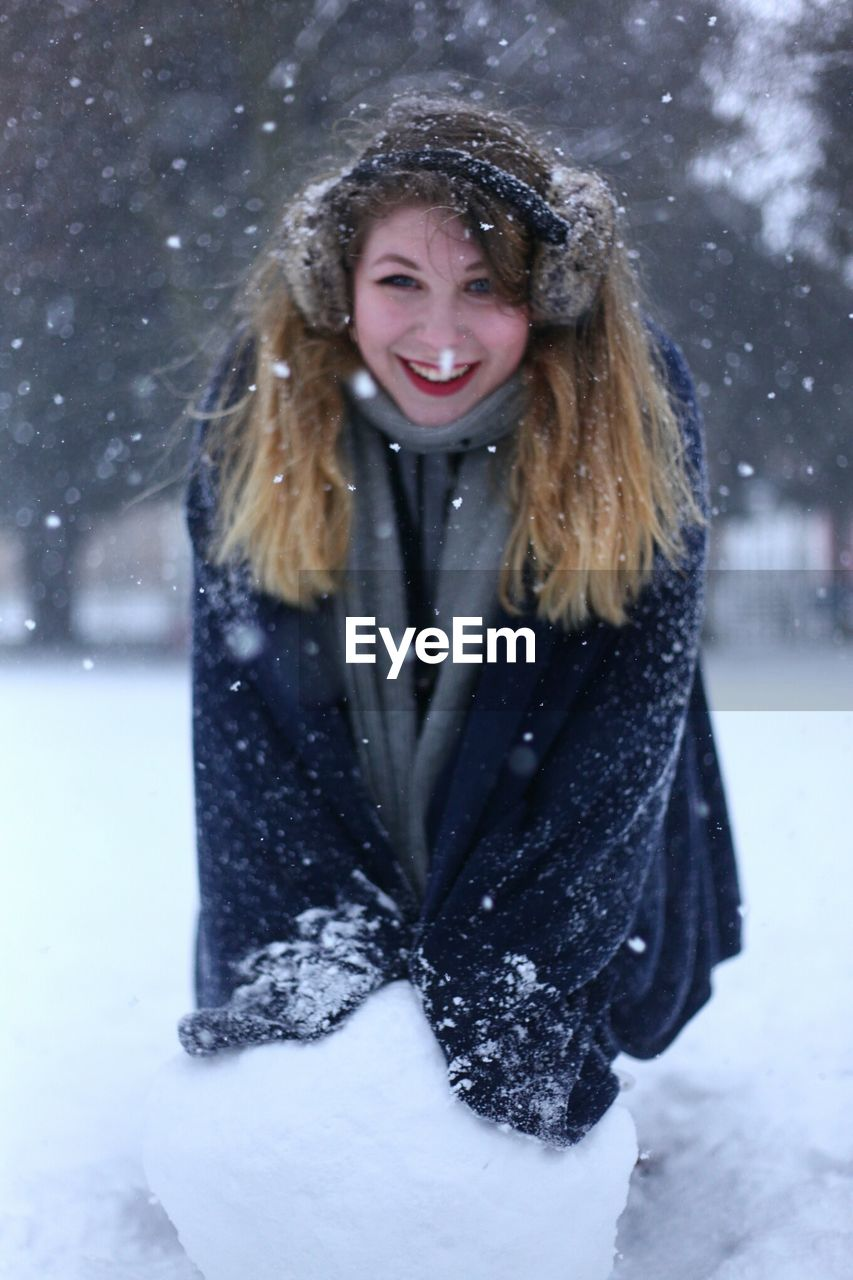 Portrait Of Smiling Young Woman On Field During Snowfall