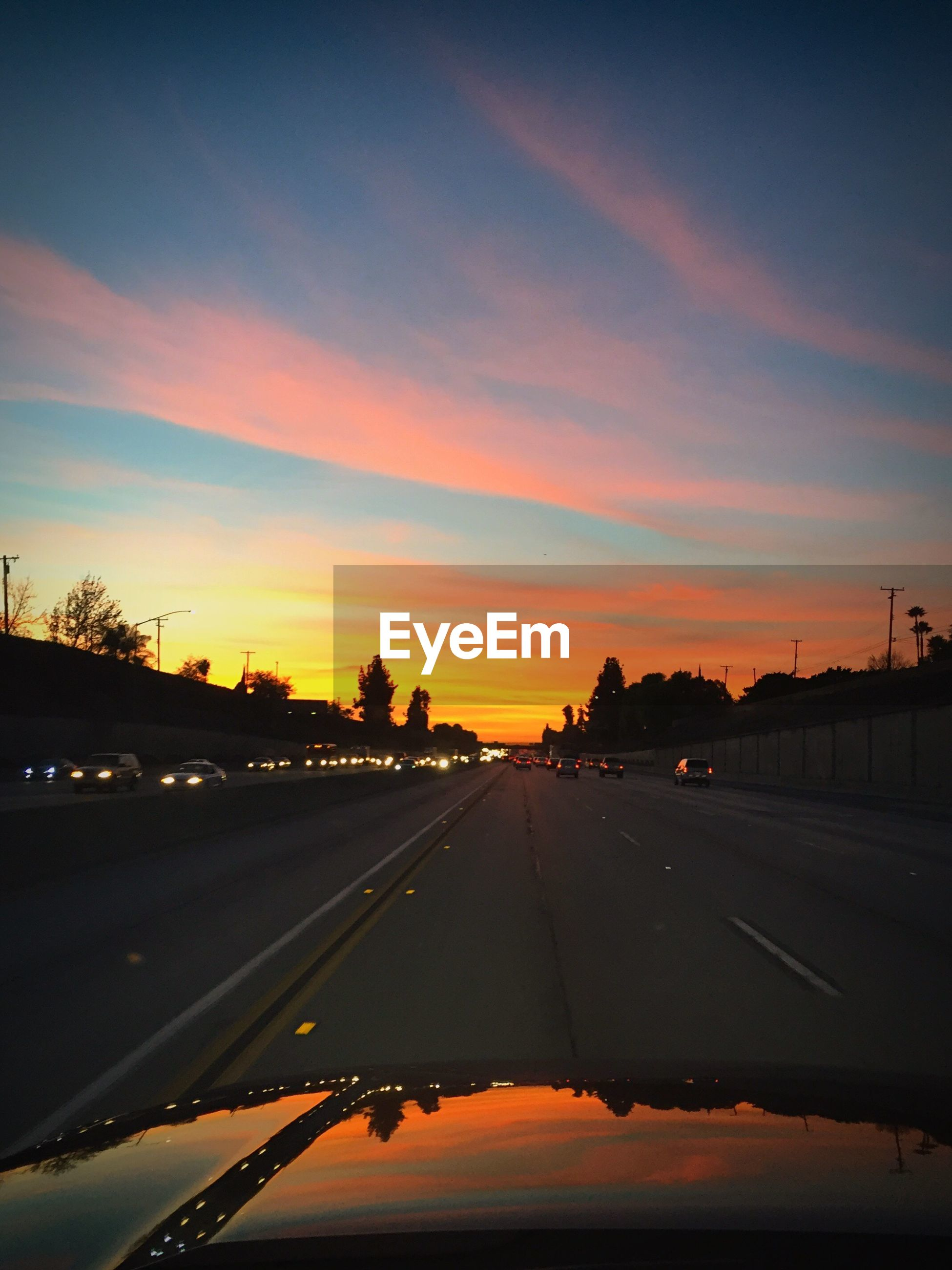 Car hood on road against sky during sunset