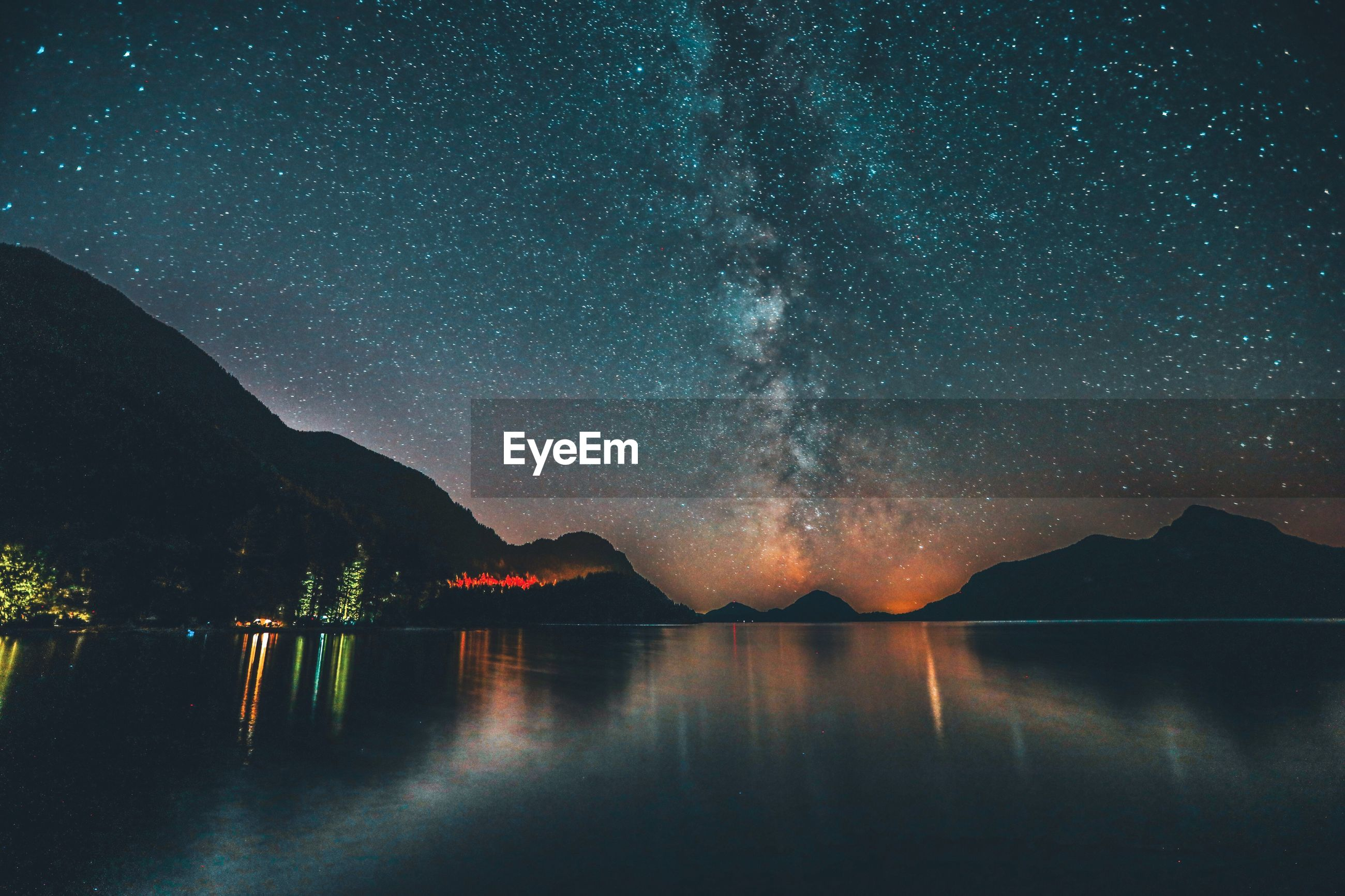 Scenic view of lake against clear sky at night