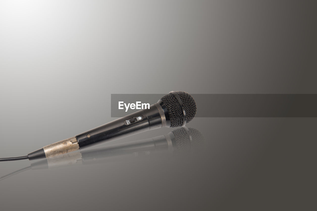 microphone, input device, indoors, close-up, studio shot, single object, still life, music, no people, copy space, technology, arts culture and entertainment, metal, white background, equipment, audio equipment, focus on foreground, communication, table, two objects, silver colored