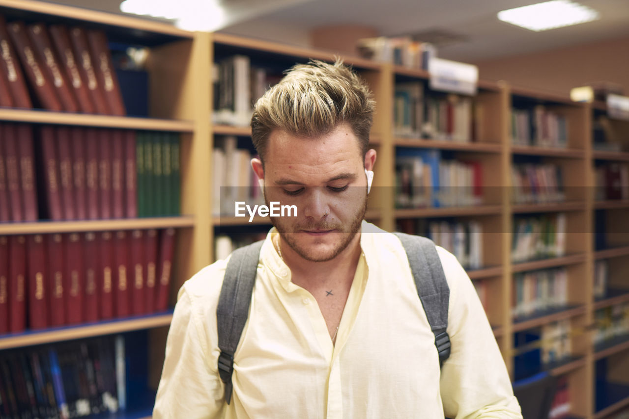 Portrait of a blond boy with headphones entering a library