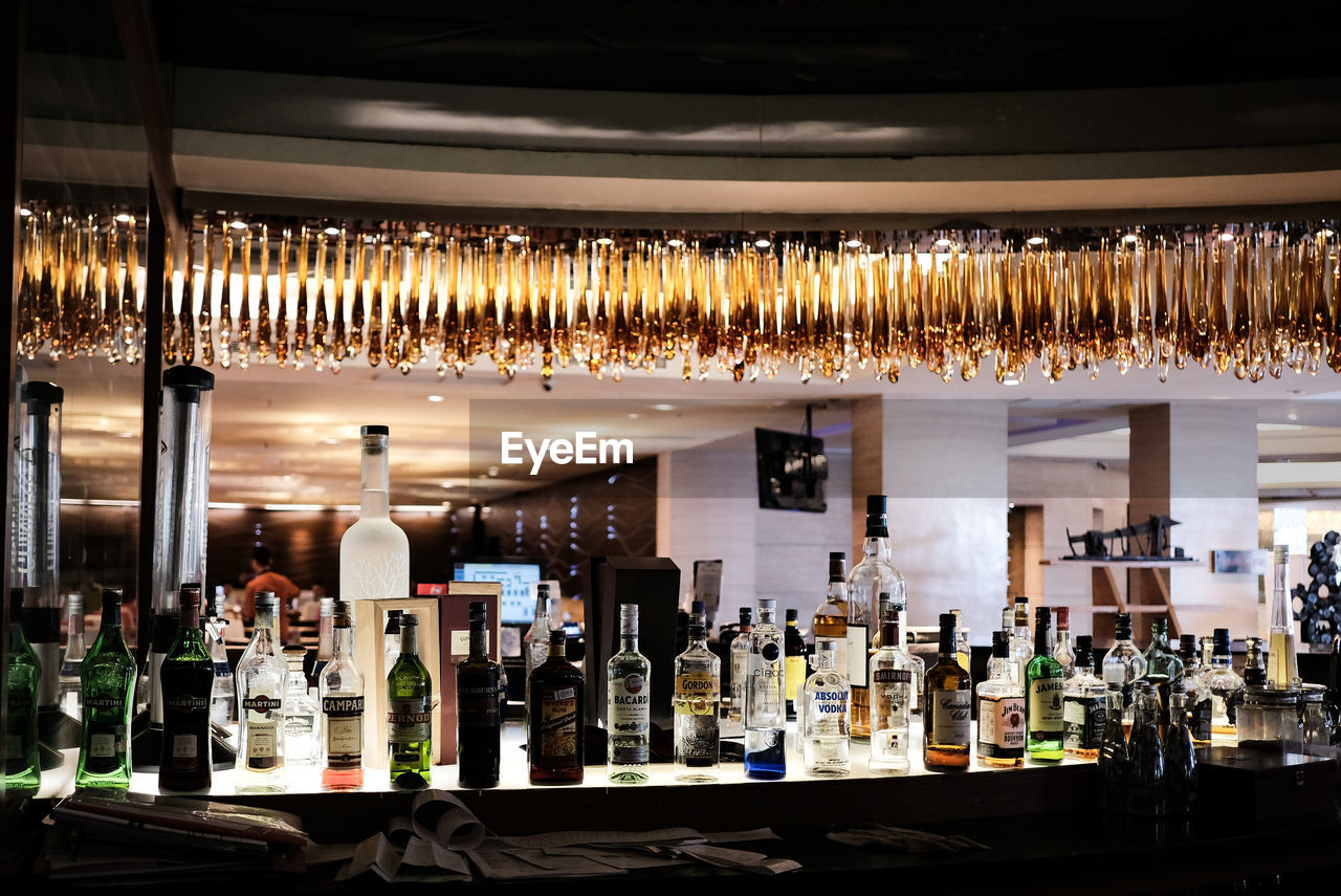 drink, bottle, alcohol, bar - drink establishment, refreshment, indoors, food and drink, container, large group of objects, illuminated, bar counter, no people, in a row, glass - material, business, hard liquor, glass, hanging, abundance, lighting equipment, nightlife, ceiling
