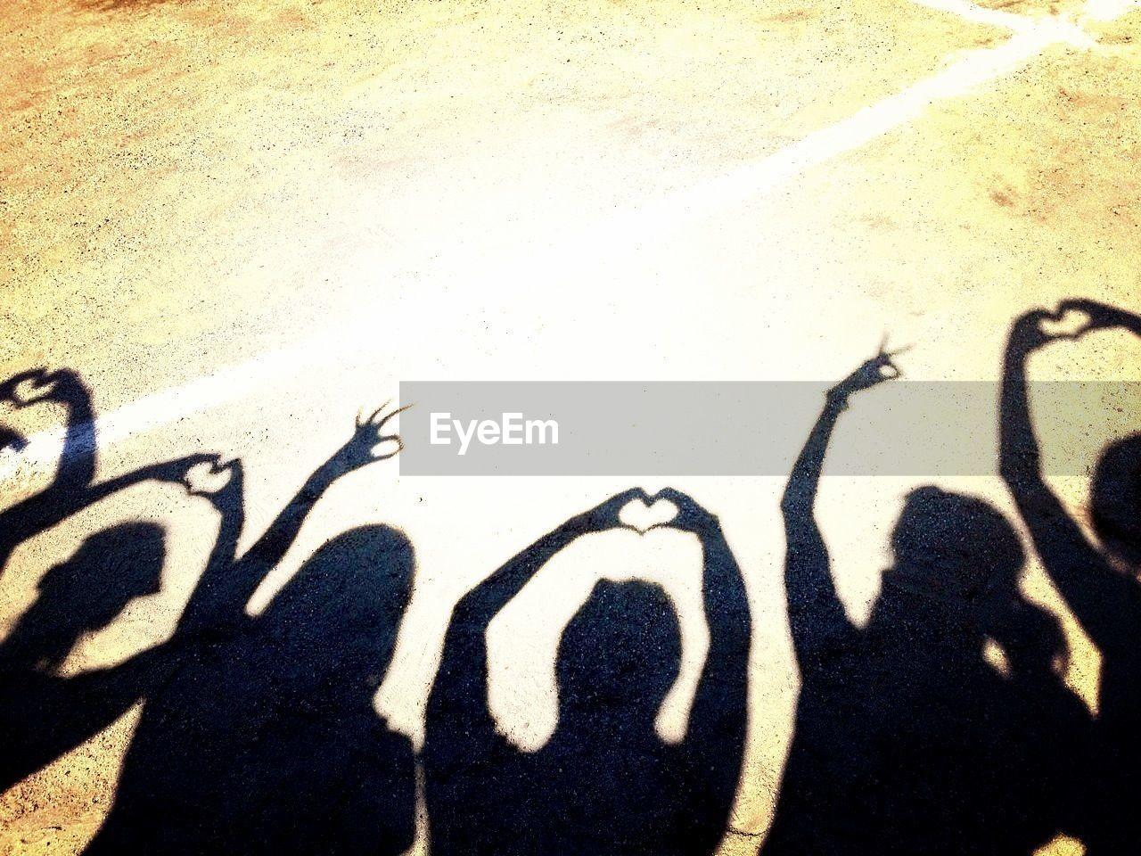 Shadows of people gesturing on ground