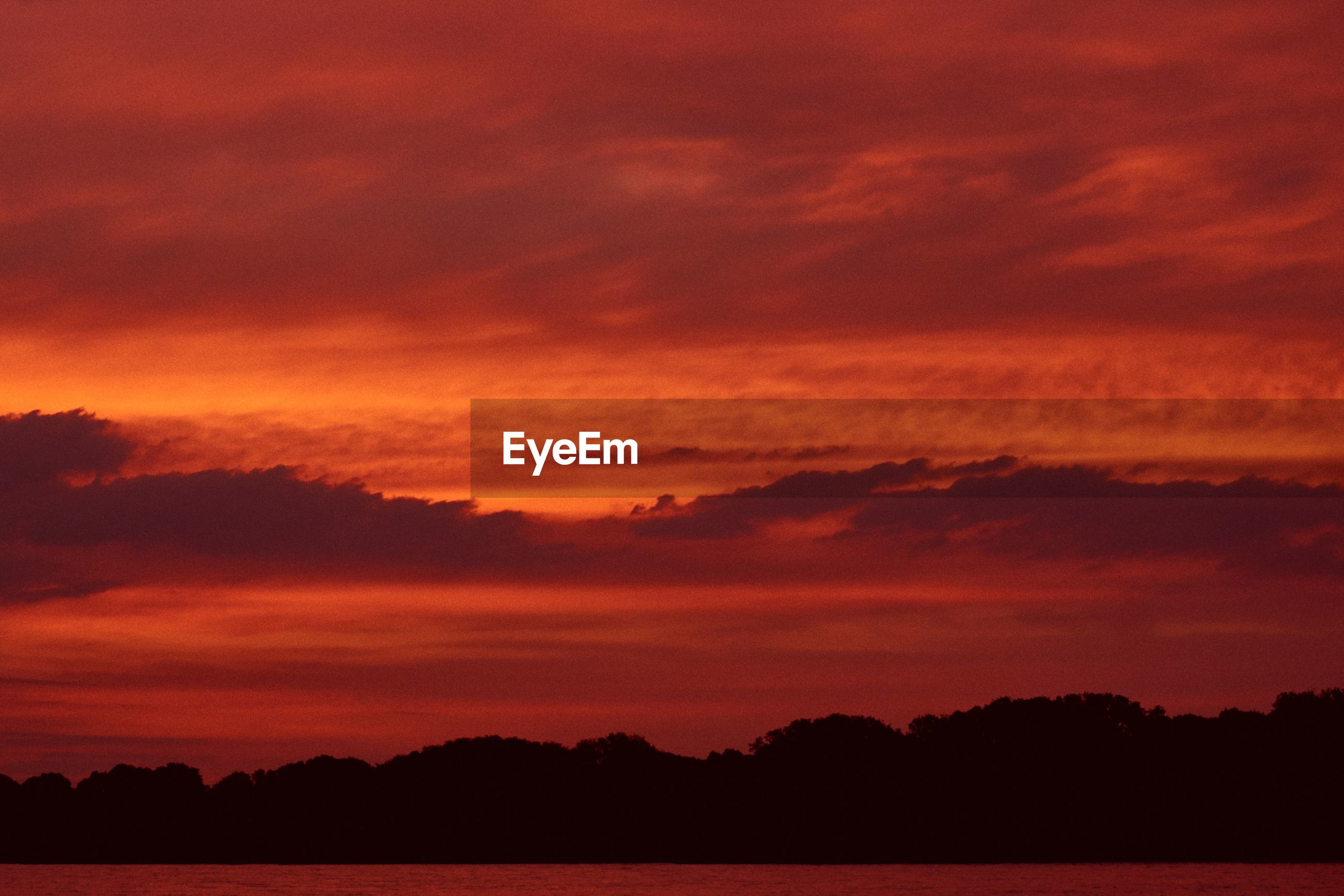 SCENIC VIEW OF DRAMATIC SKY OVER SILHOUETTE LANDSCAPE DURING SUNSET