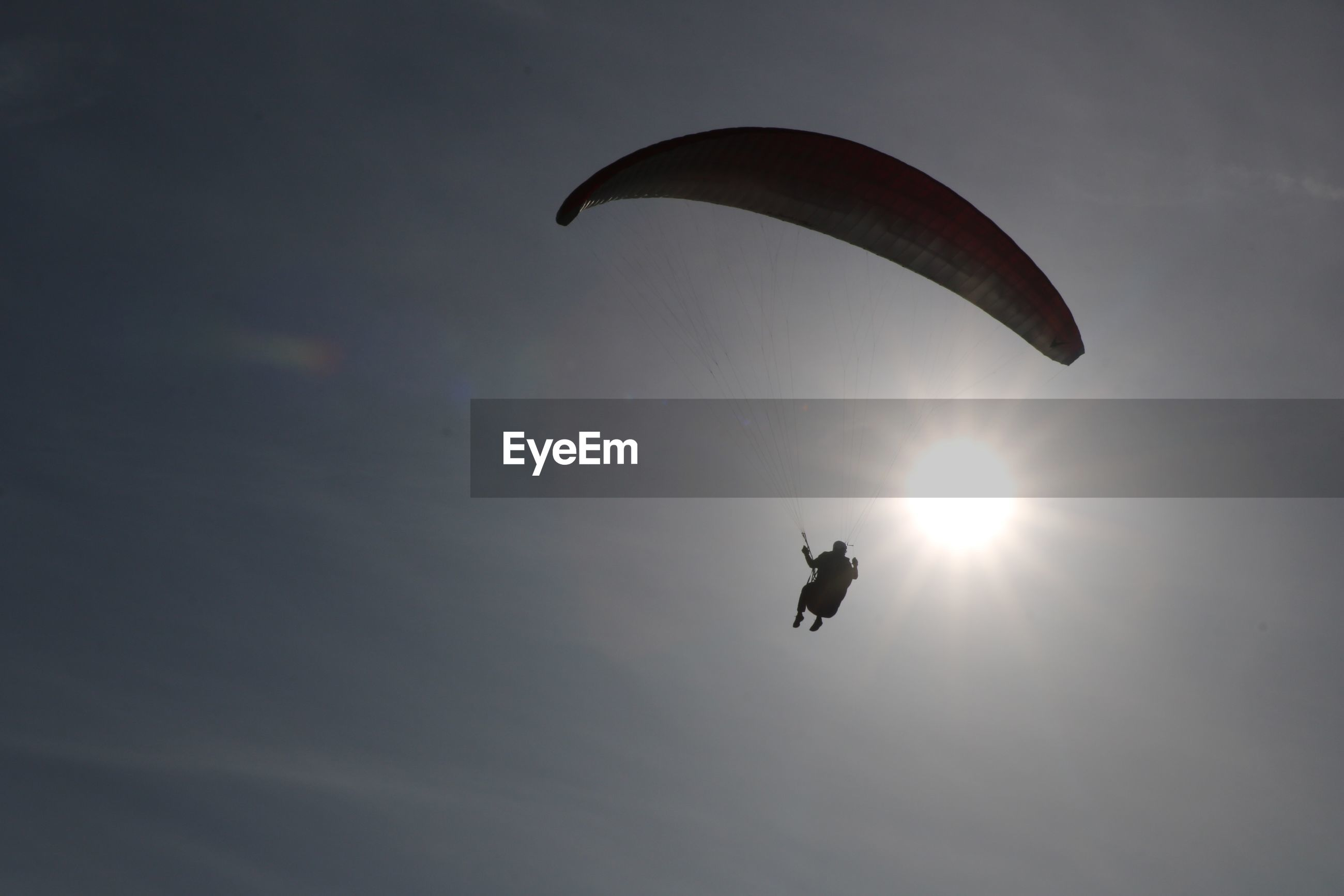 Low angle view of silhouette person paragliding against sky