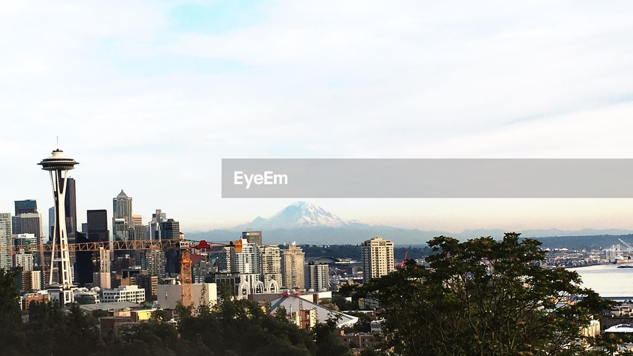 cityscape, architecture, mountain, building exterior, city, built structure, crowded, sky, travel destinations, skyscraper, outdoors, cloud - sky, day, sea, scenics, nature, urban skyline, beauty in nature, tree, modern