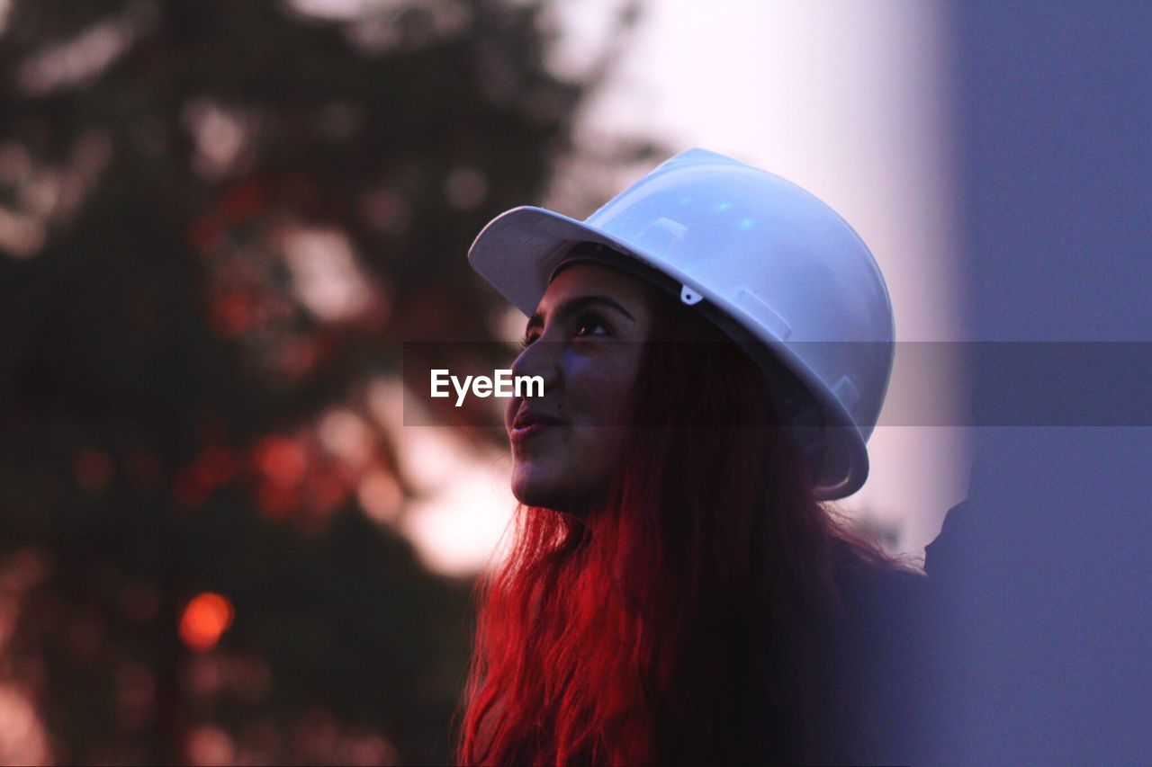 Close-up of young woman wearing hardhat during sunset