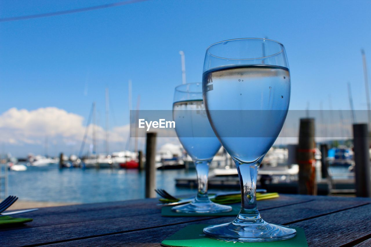 glass, water, sky, focus on foreground, nature, day, drink, no people, wineglass, food and drink, table, nautical vessel, refreshment, blue, glass - material, transparent, clear sky, transportation, close-up, outdoors
