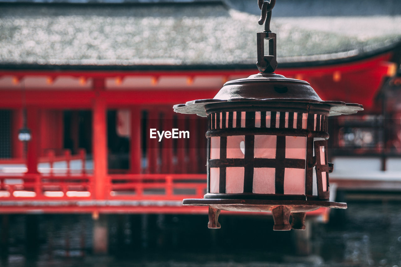 red, hanging, focus on foreground, no people, outdoors, close-up, day, lantern, place of worship, architecture