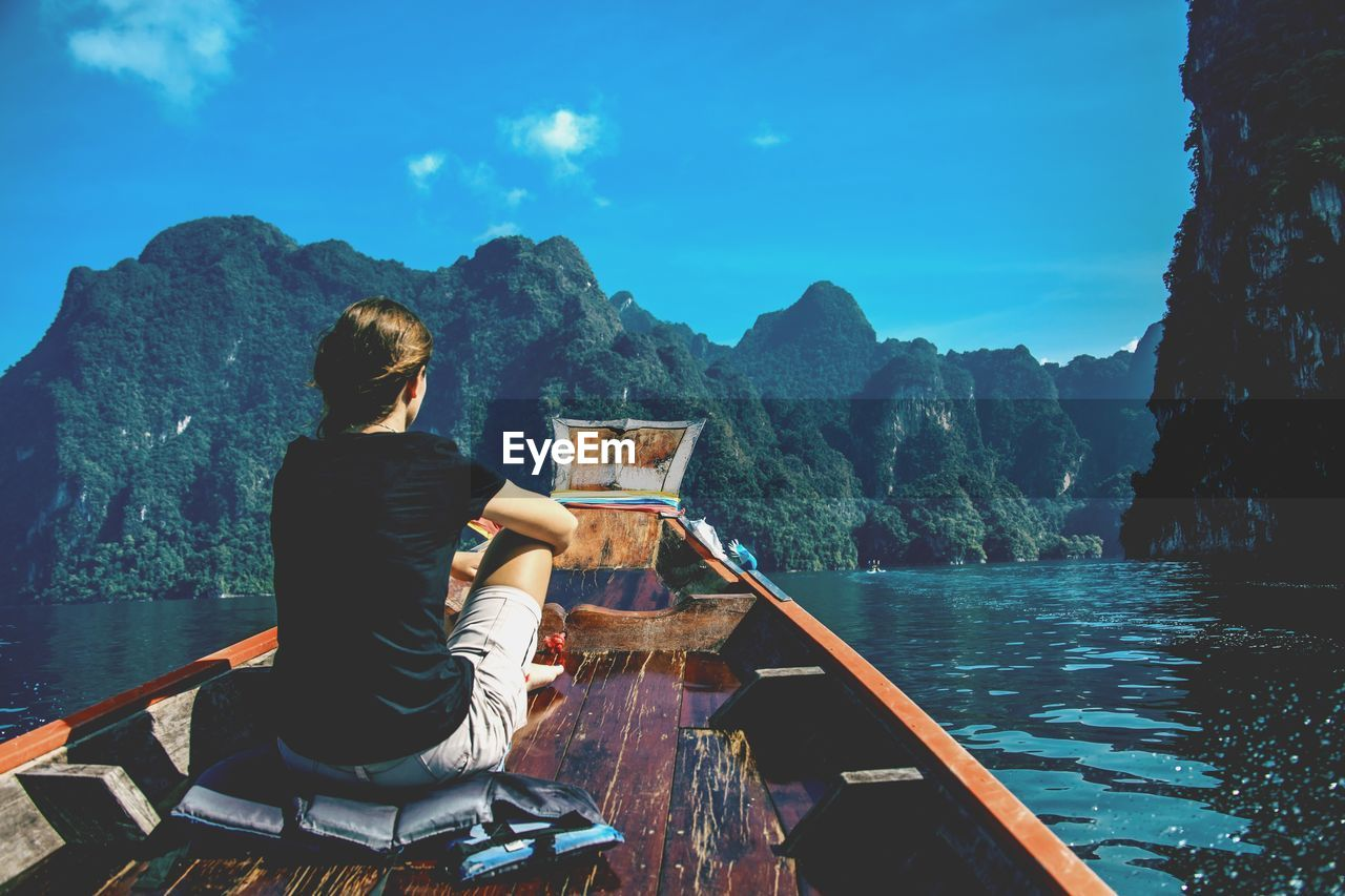 water, sitting, one person, real people, lifestyles, leisure activity, nature, mountain, beauty in nature, sky, scenics - nature, day, rear view, adult, tranquility, sea, young adult, casual clothing, mountain range, outdoors