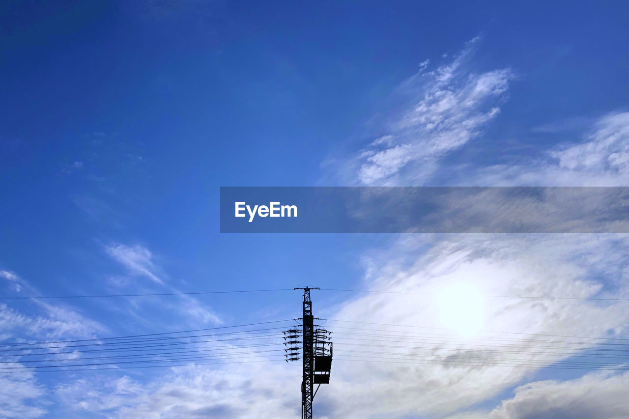 sky, cloud - sky, technology, low angle view, electricity, cable, connection, no people, power supply, electricity pylon, blue, nature, power line, fuel and power generation, day, outdoors, communication, sunlight, lighting equipment, electrical equipment, telephone line