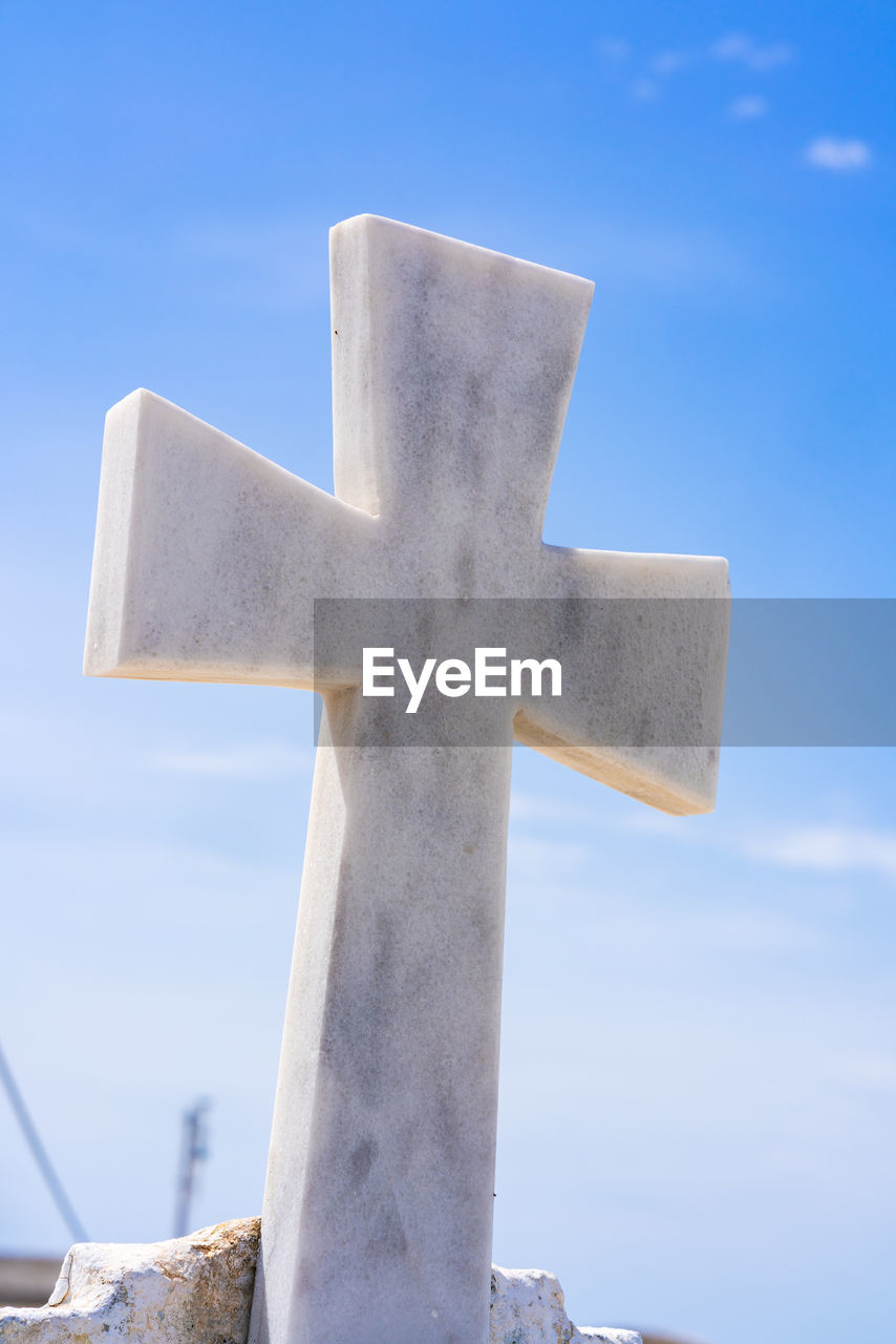religion, spirituality, belief, cross, sky, blue, no people, day, low angle view, symbol, cross shape, outdoors, nature, focus on foreground, stone, grave, crucifix