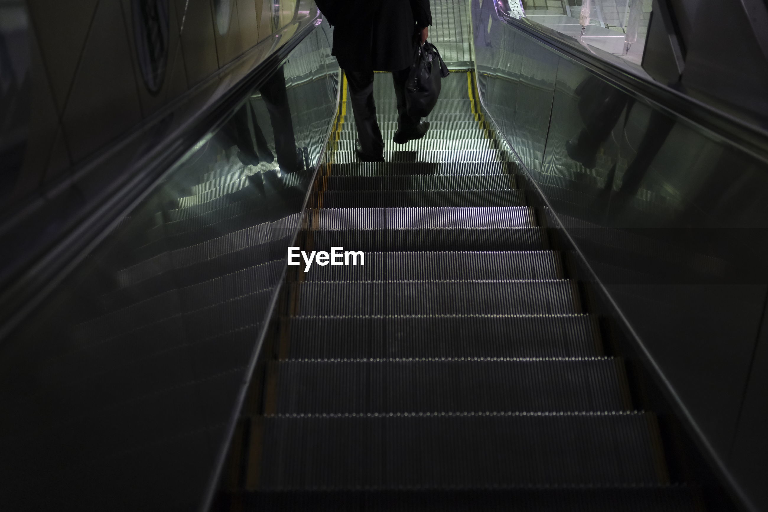LOW SECTION OF MAN MOVING DOWN ON ESCALATOR