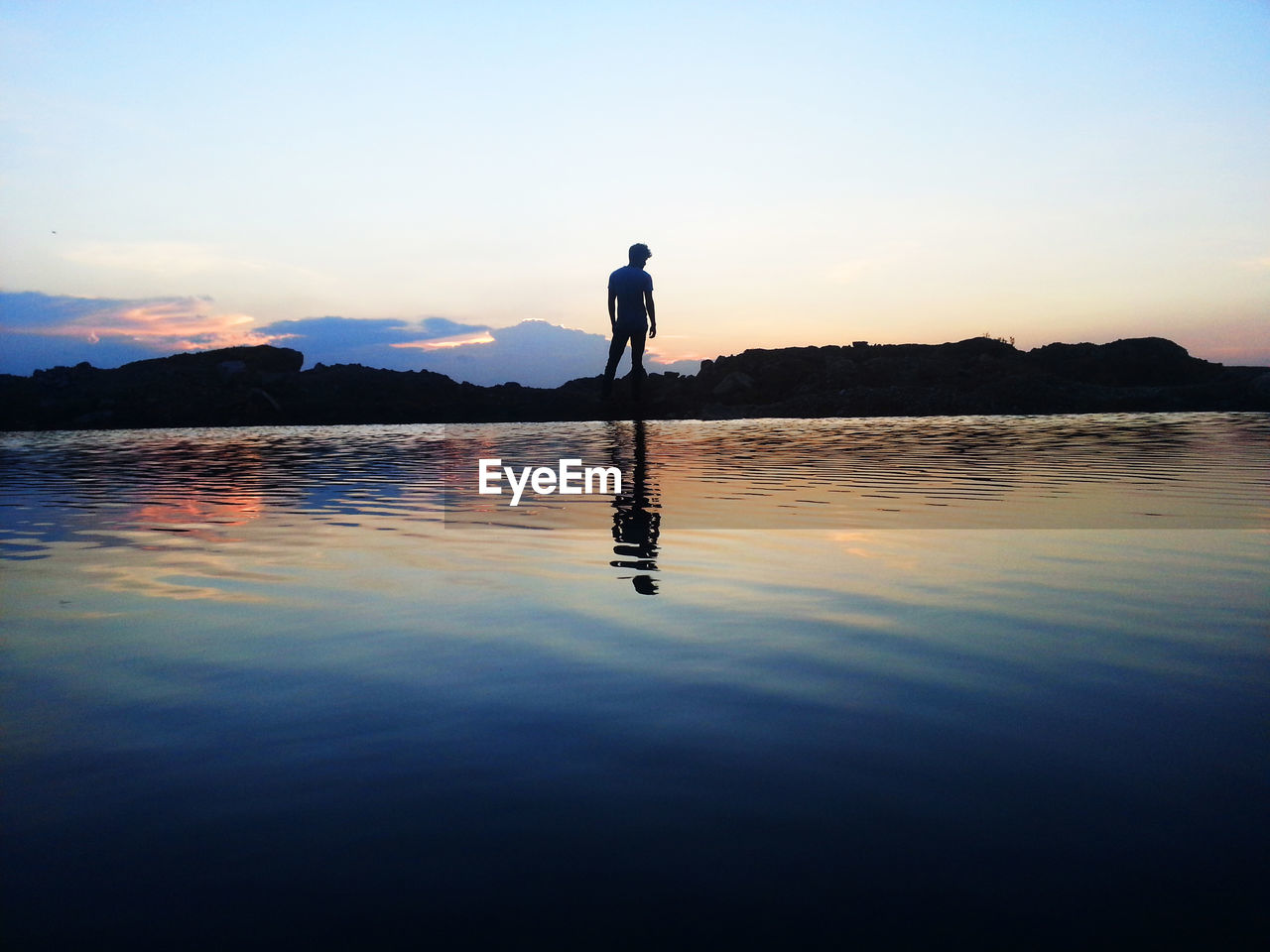full length, sunset, one person, reflection, real people, tranquil scene, water, silhouette, scenics, beauty in nature, nature, leisure activity, outdoors, lake, sky, tranquility, lifestyles, standing, clear sky, vacations, men, ankle deep in water, day, people