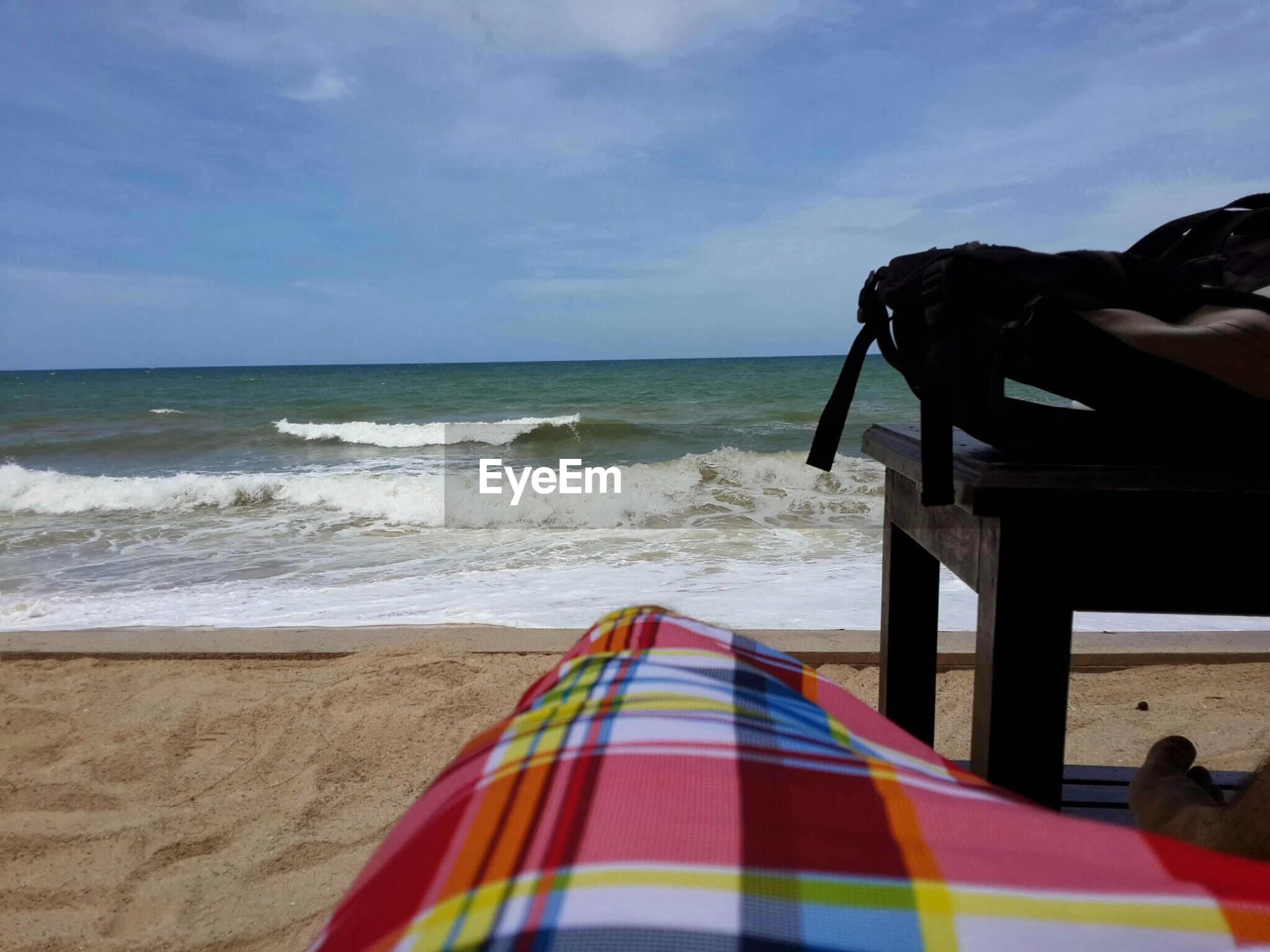 Multi colored blanket by bag on table at sandy beach