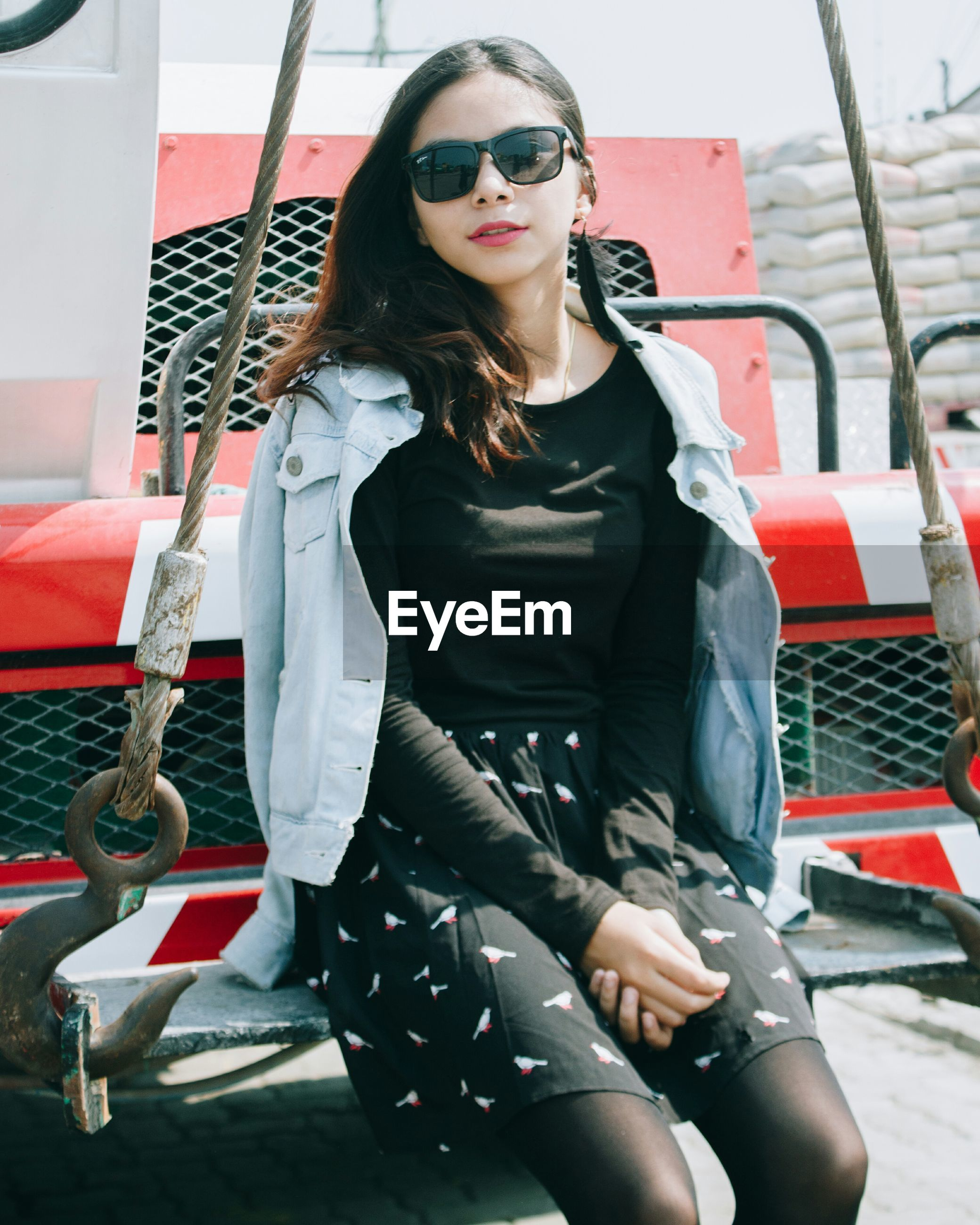 young adult, real people, three quarter length, sunglasses, young women, one person, front view, sitting, fashion, beautiful woman, lifestyles, jacket, leisure activity, casual clothing, full length, posing, medium-length hair, looking at camera, portrait, day, happiness, outdoors