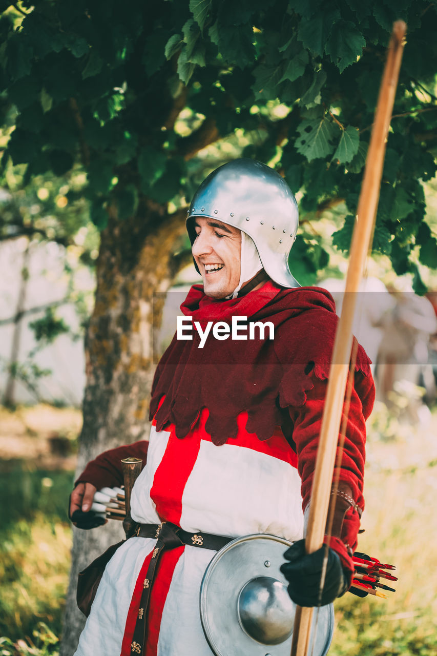 real people, one person, tree, men, lifestyles, leisure activity, day, nature, clothing, males, three quarter length, emotion, waist up, smiling, focus on foreground, happiness, front view, looking away, adult, outdoors, riding