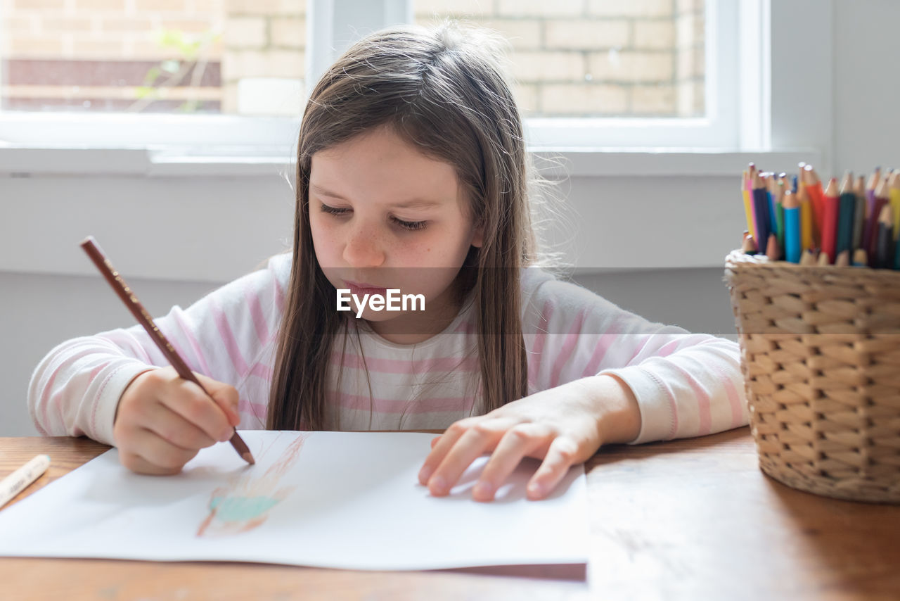 Girl Drawing On Paper While Sitting On Table At Home
