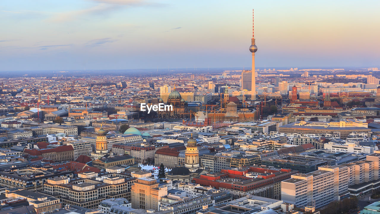Fernsehturm Amidst Cityscape Against Sky During Sunset