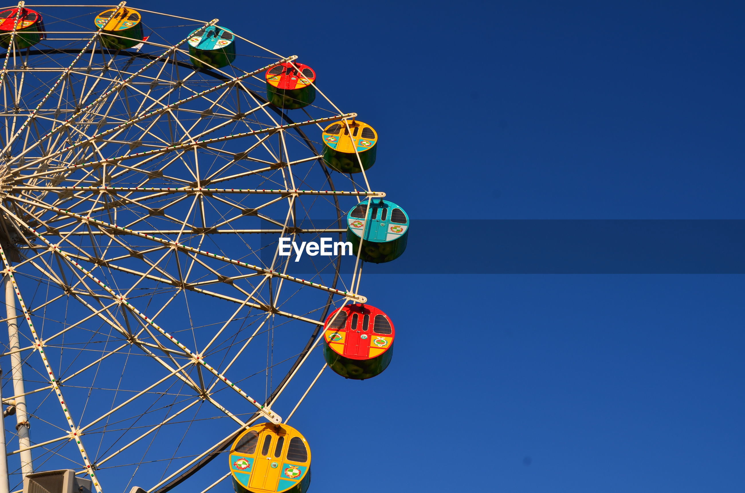 Low angle view of ferris wheel against clear blue sky