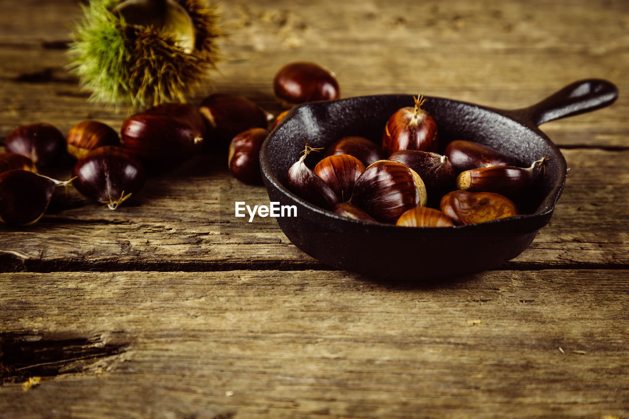 food, food and drink, table, wood - material, freshness, still life, healthy eating, no people, wellbeing, chestnut, brown, indoors, chestnut - food, close-up, selective focus, nut - food, bowl, fruit, nut, large group of objects