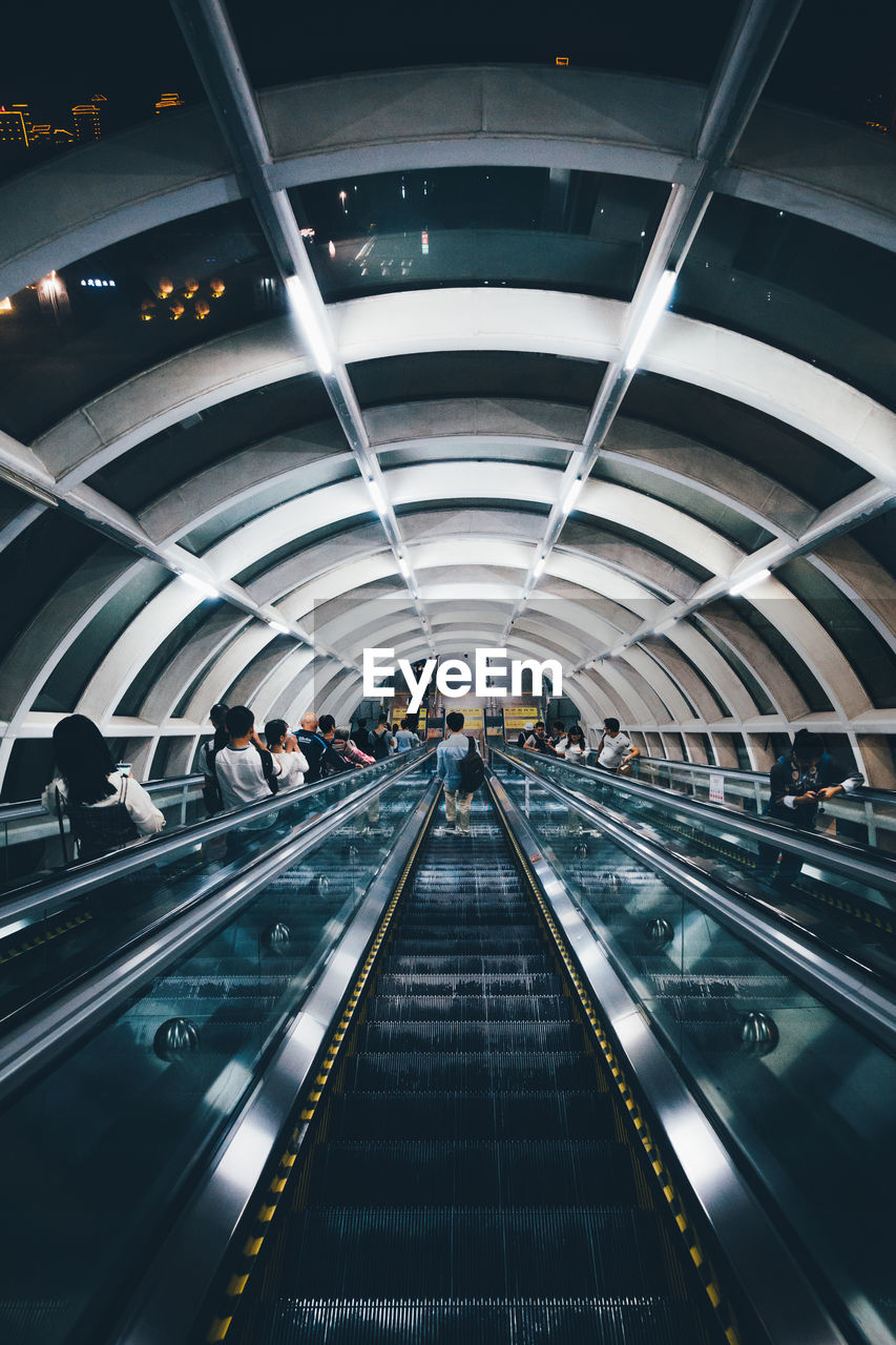 architecture, transportation, illuminated, indoors, real people, convenience, travel, group of people, lifestyles, moving walkway, modern, ceiling, arch, lighting equipment, escalator, technology, incidental people, men, direction, subway station, diminishing perspective, light