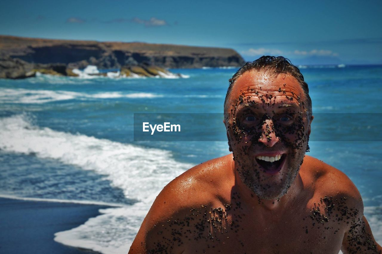 sea, water, shirtless, one person, real people, portrait, headshot, lifestyles, beach, sunlight, looking at camera, land, males, mid adult, front view, nature, men, leisure activity, outdoors, mature men, horizon over water