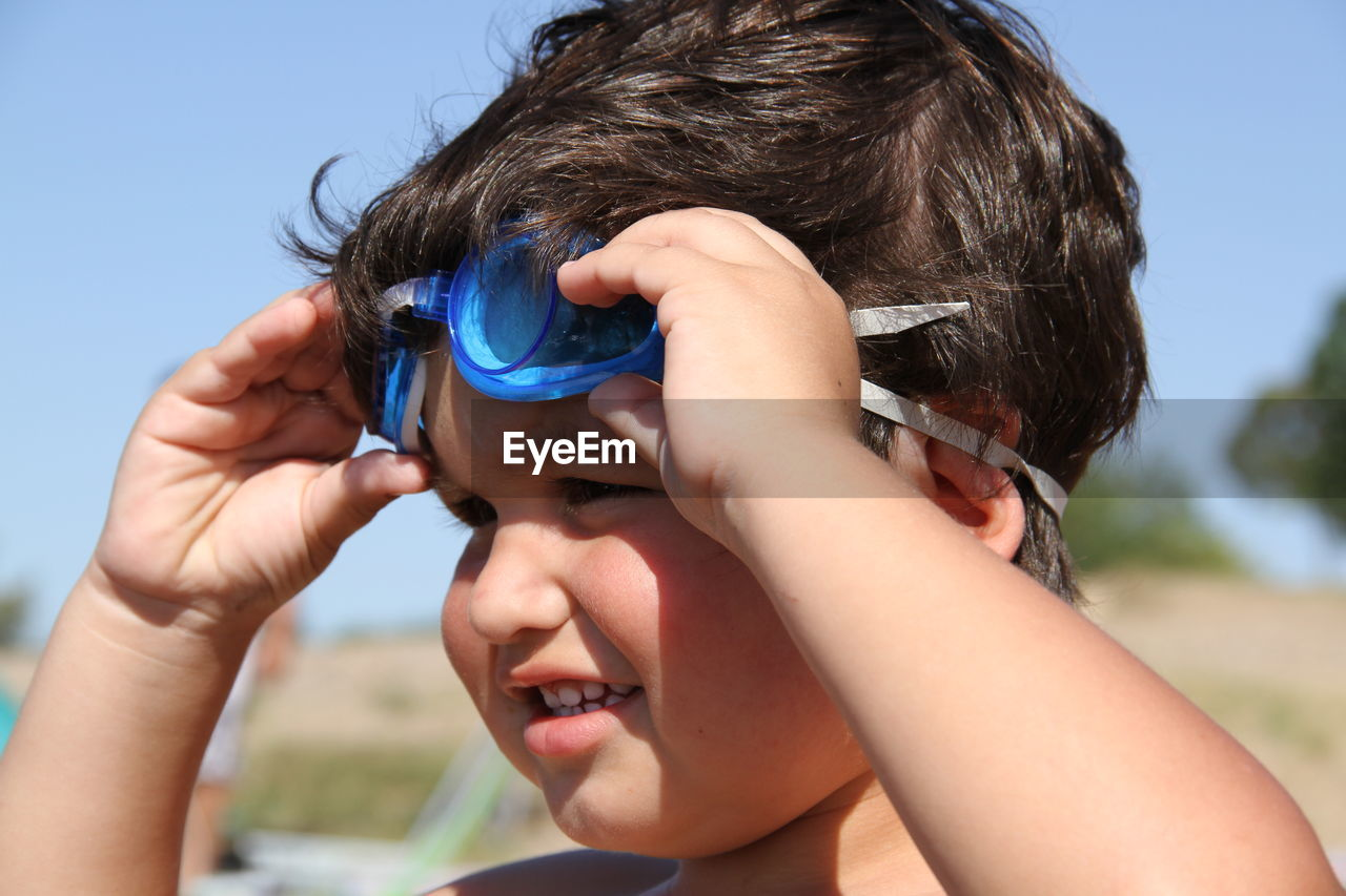 Close-Up Of Boy Wearing Swimming Goggles Against Sky