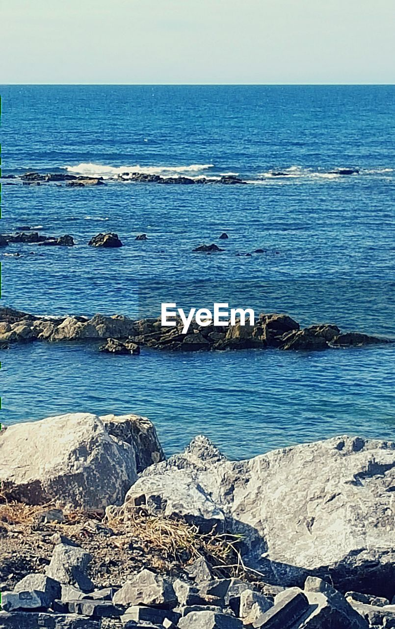 sea, horizon over water, rock - object, beach, water, nature, outdoors, scenics, beauty in nature, no people, rocky coastline, blue, travel destinations, day, sky, clear sky, groyne