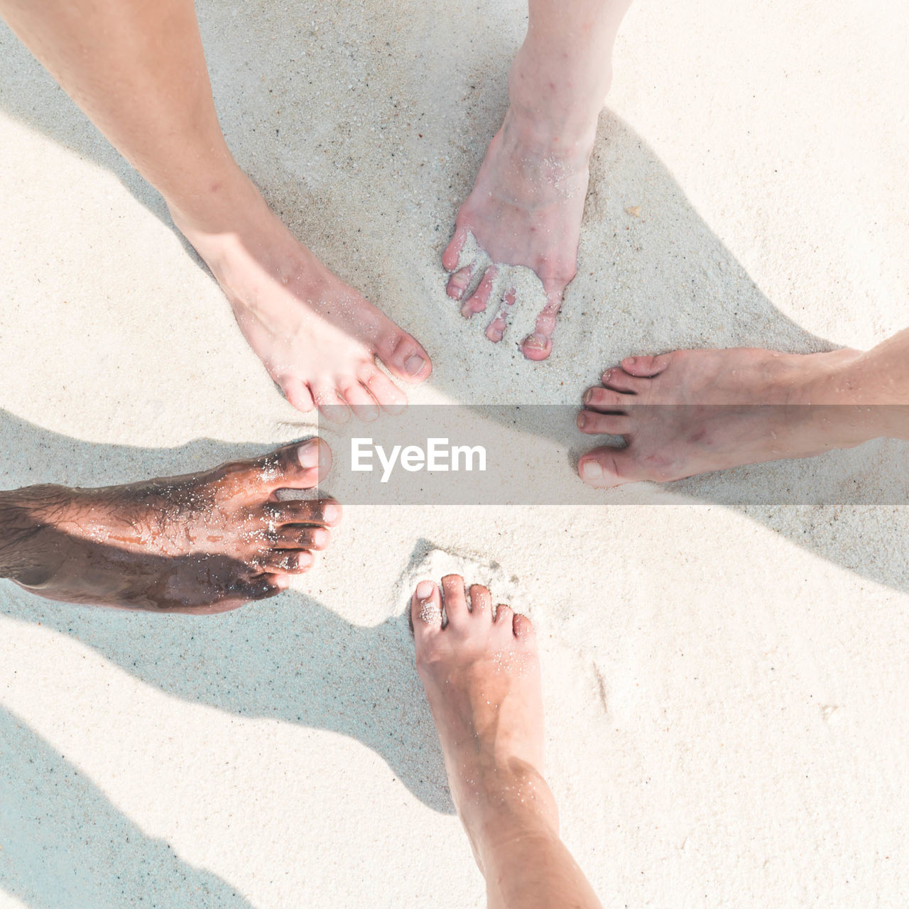 human body part, beach, land, sand, togetherness, body part, nature, sunlight, high angle view, barefoot, day, human leg, low section, standing, people, leisure activity, group of people, shadow, real people, vacations, human foot, outdoors, positive emotion, human limb