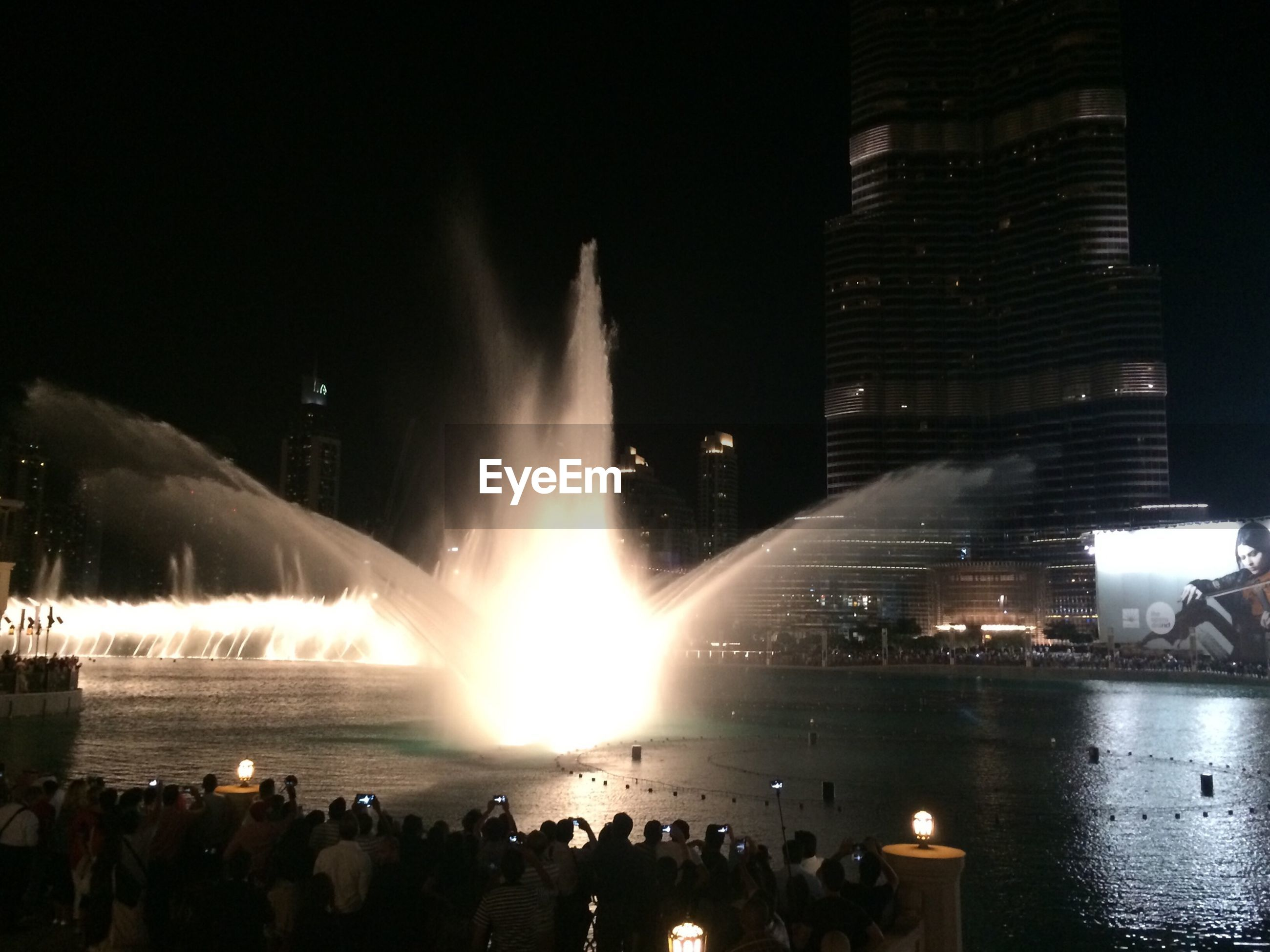 water, city, reflection, building exterior, architecture, built structure, night, illuminated, silhouette, city life, river, waterfront, large group of people, cityscape, sky, men, skyscraper, lifestyles, modern