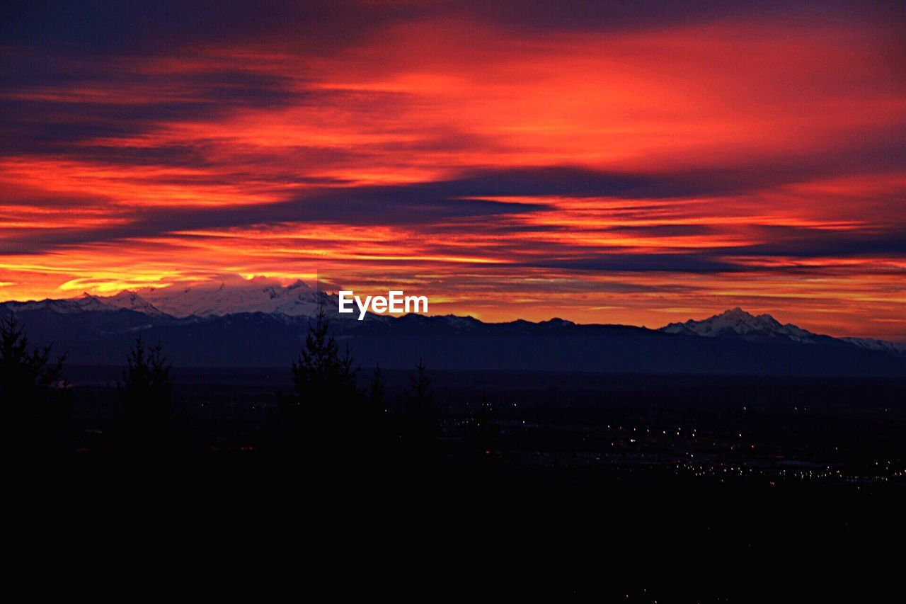 Silhouette landscape against cloudy orange sky