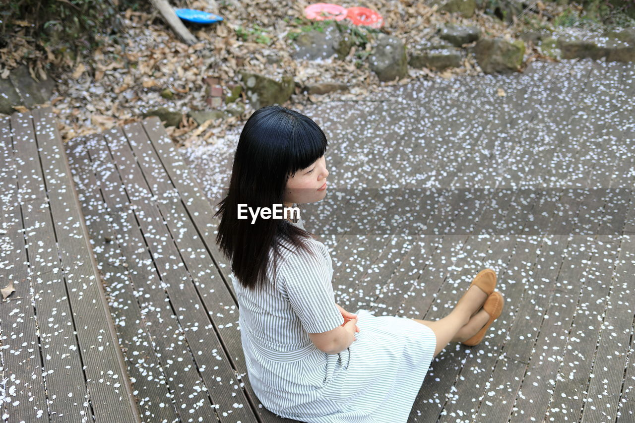 High angle view of woman looking away while sitting on staircase