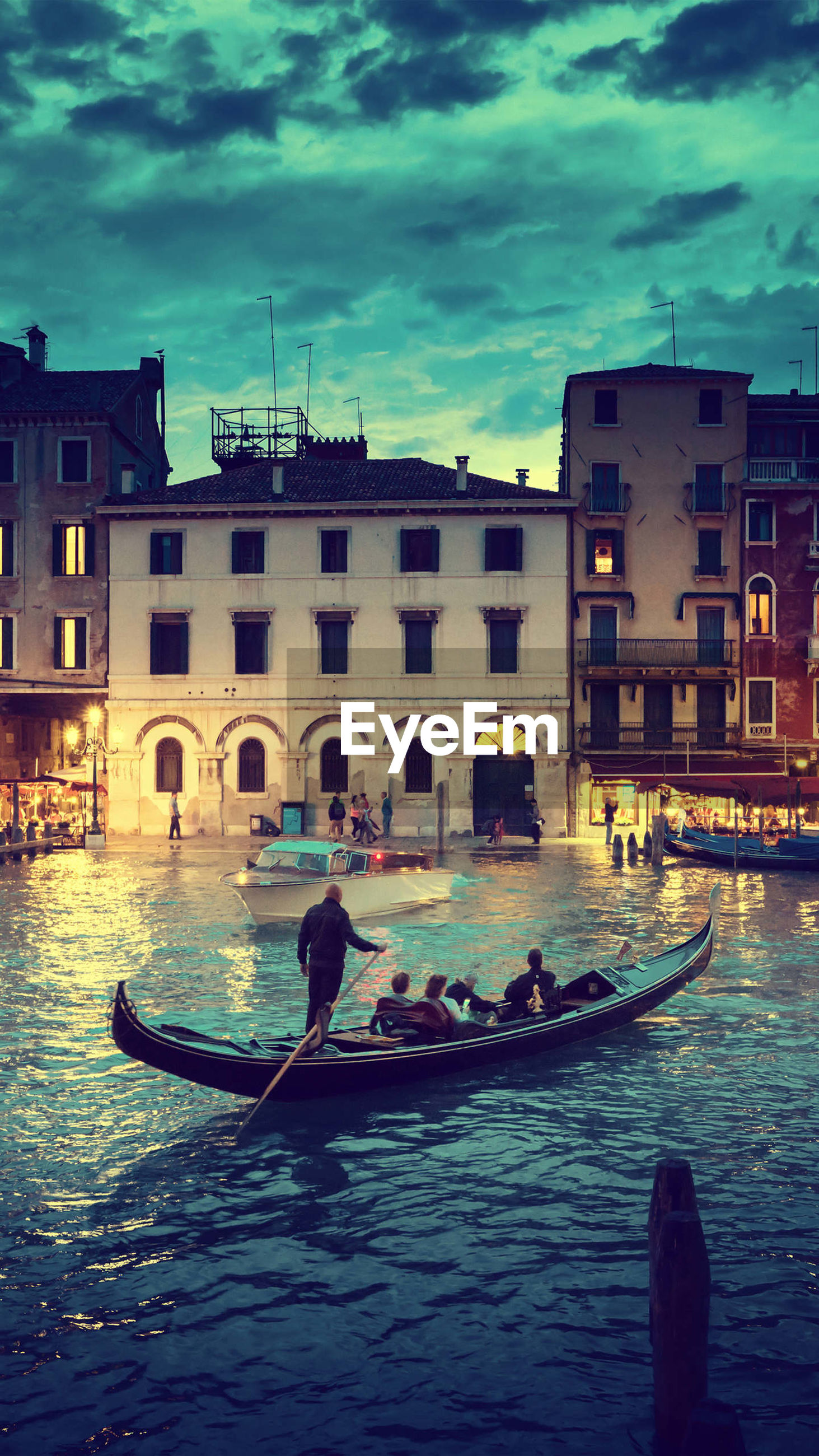 gondola - traditional boat, architecture, canal, transportation, gondolier, building exterior, nautical vessel, built structure, gondola, men, real people, mode of transport, oar, travel, day, outdoors, rowing, travel destinations, water, sitting, standing, sky, one person, adult, people