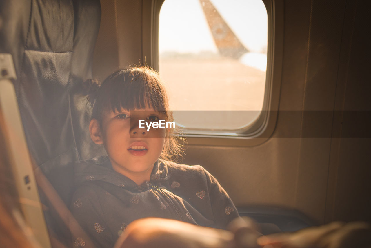 Portrait of girl traveling in airplane during sunset
